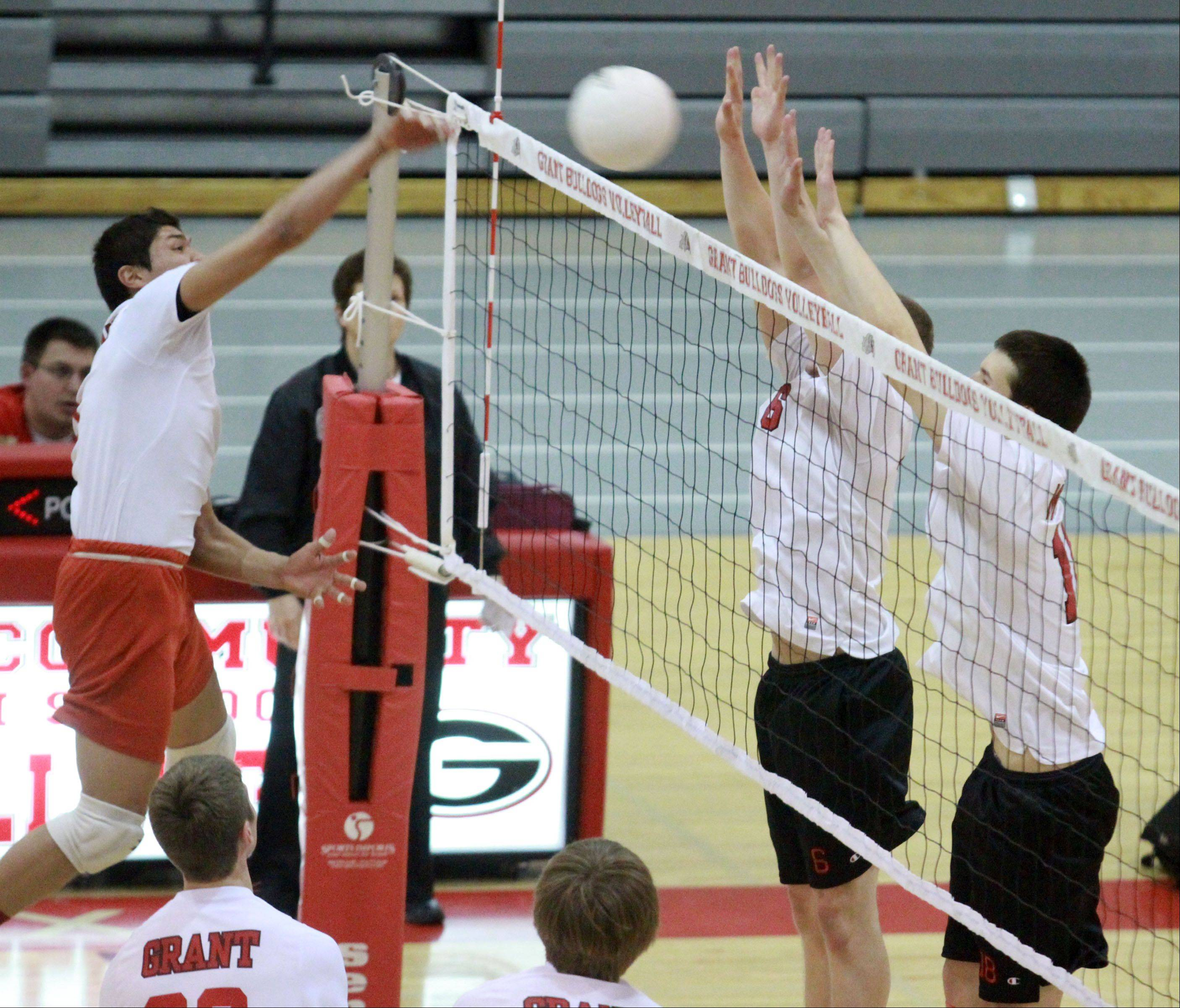 Grant's Ron Torres goes for a kill as Mundelein's Christian Brubaker, left, and Joey Tylka set up the block at Grant on Friday.