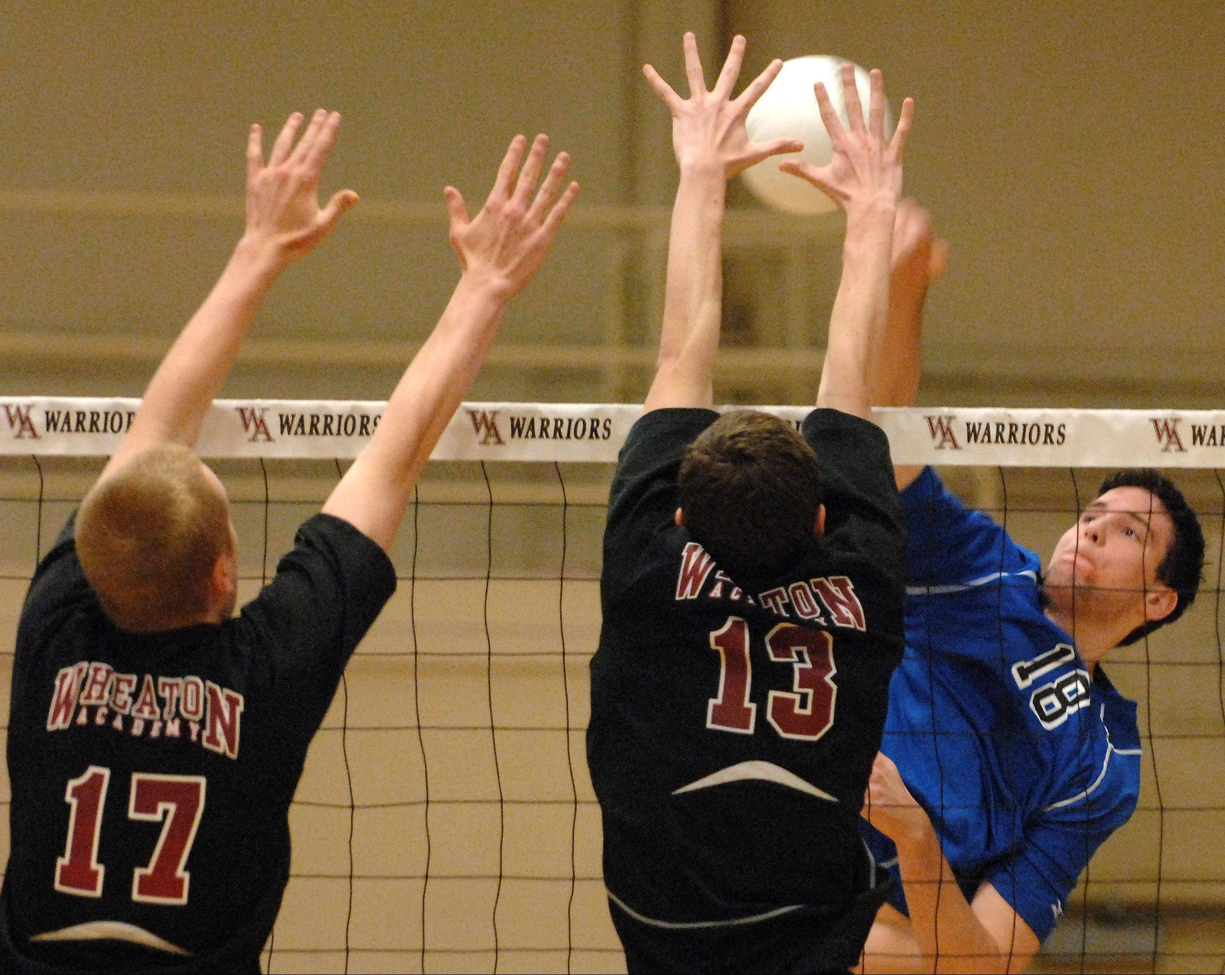 Geneva's Nick Buseki tries to squeeze a shot between Wheaton Academy blockers Steven McDonell, left, and Jeremy Vischer during volleyball action at Wheaton Academy in West Chicago Friday.