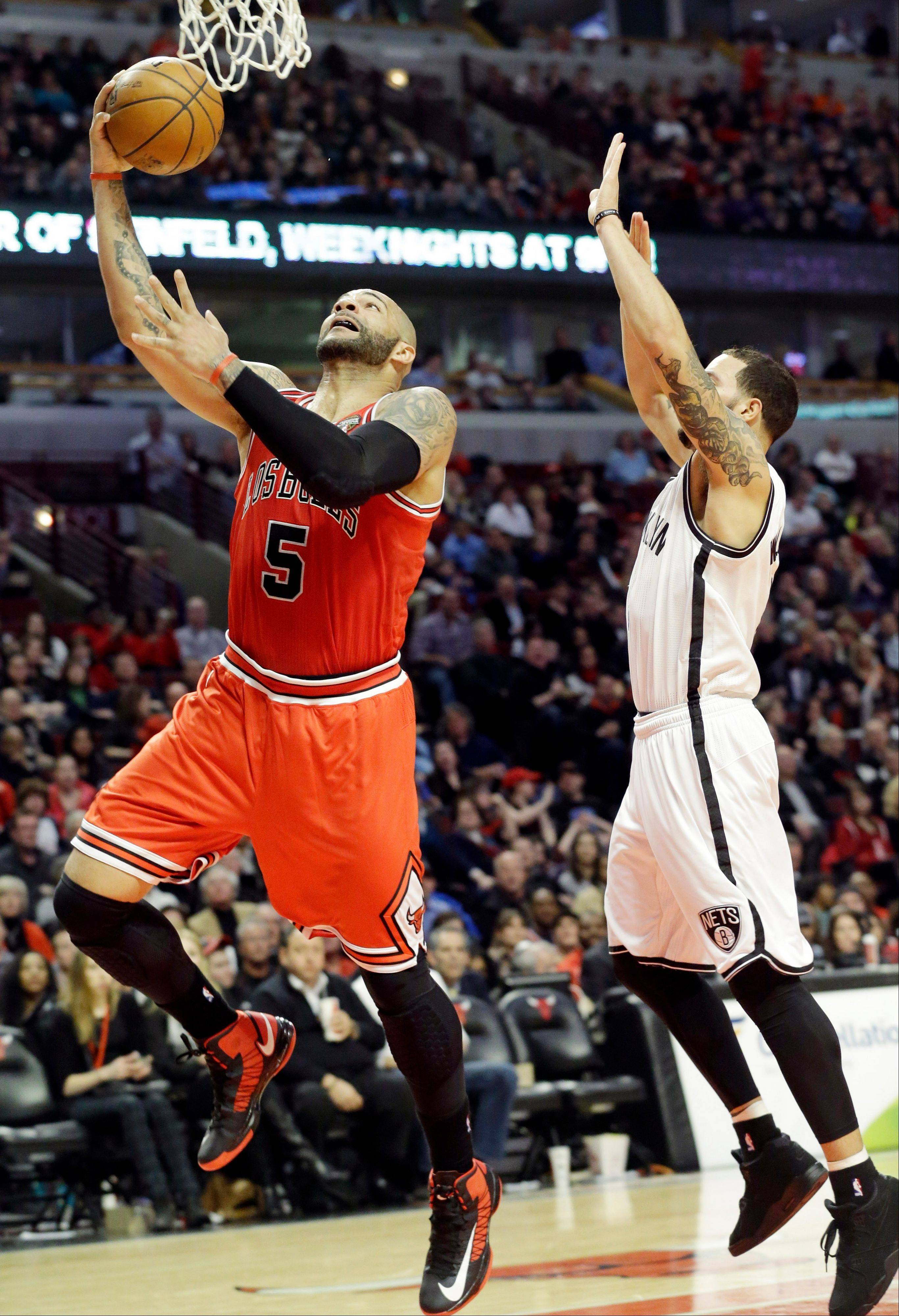 Bulls forward Carlos Boozer drives to the basket past Brooklyn Nets guard Deron Williams.