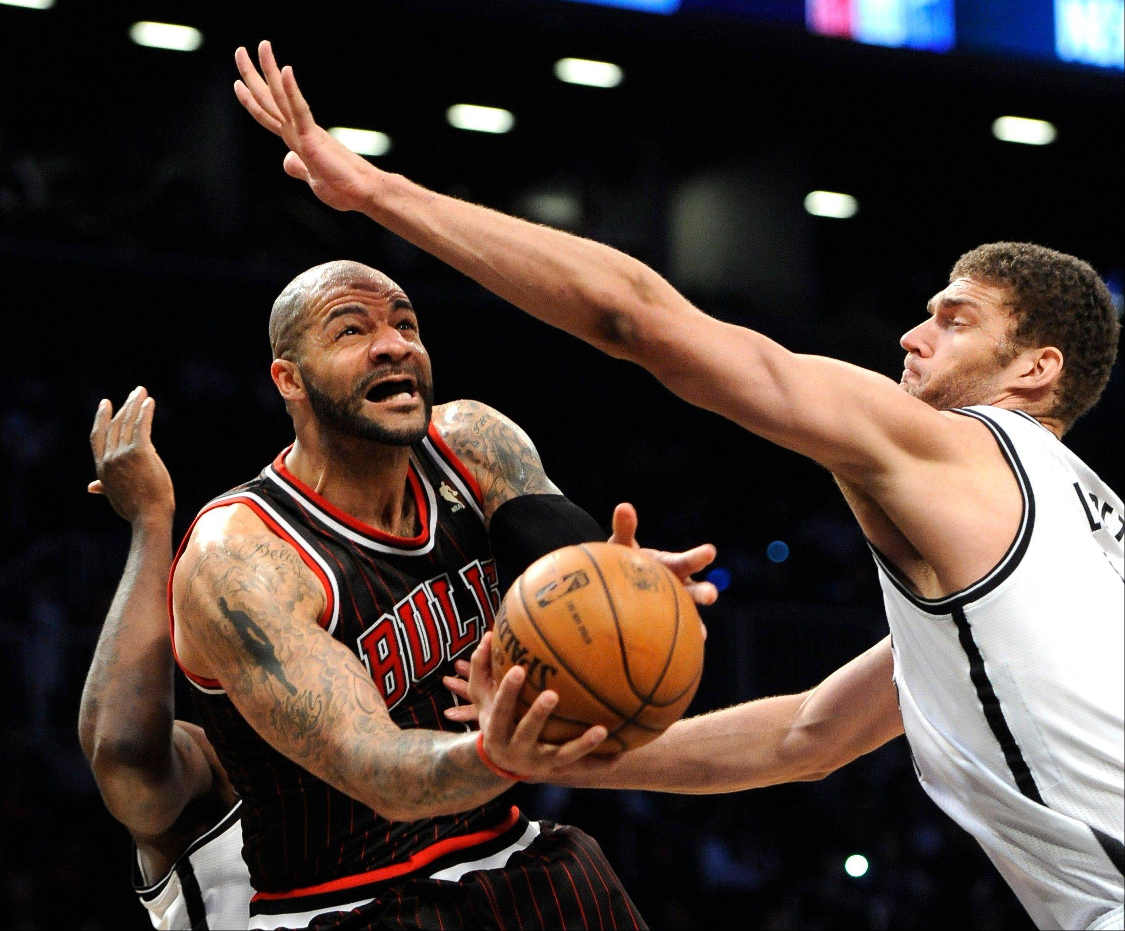 The Bulls' Carlos Boozer, left, tries to maneuver under pressure from Brook Lopez of the Brooklyn Nets.