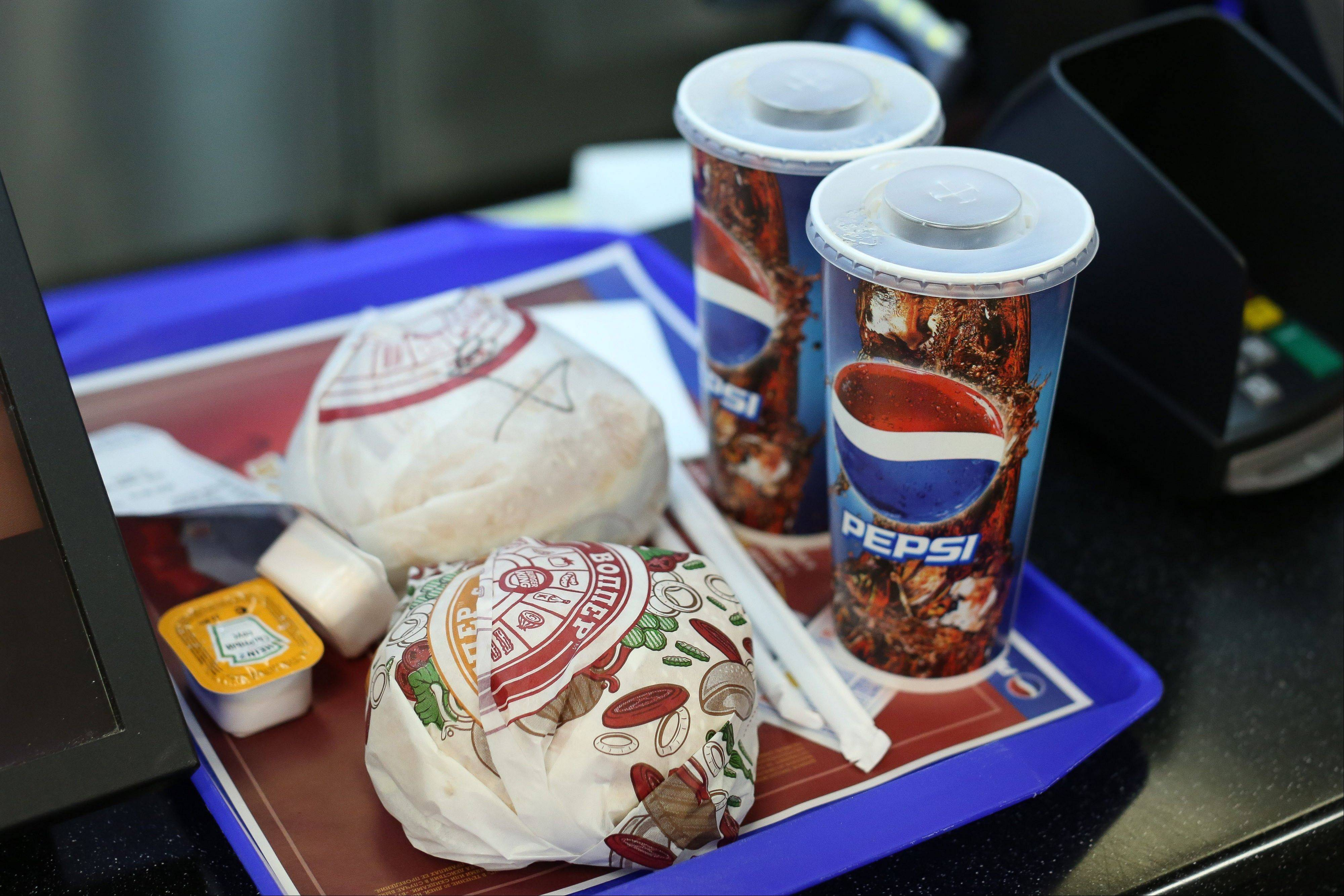 A burger king meal, which includes hamburgers and Pepsi soft drinks, sits on a tray inside a Burger King fast food restaurant in Moscow, Russia.