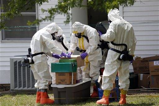 Federal agents wearing hazardous material suits and breathing apparatus inspect the home and possessions in the West Hills Subdivision house of Paul Kevin Curtis in Corinth, Miss., Friday, April 19, 2013. Curtis is in custody under the suspicion of sending letters covered in ricin to the U.S. President Barack Obama and U.S. Sen. Roger Wicker, R-Miss.
