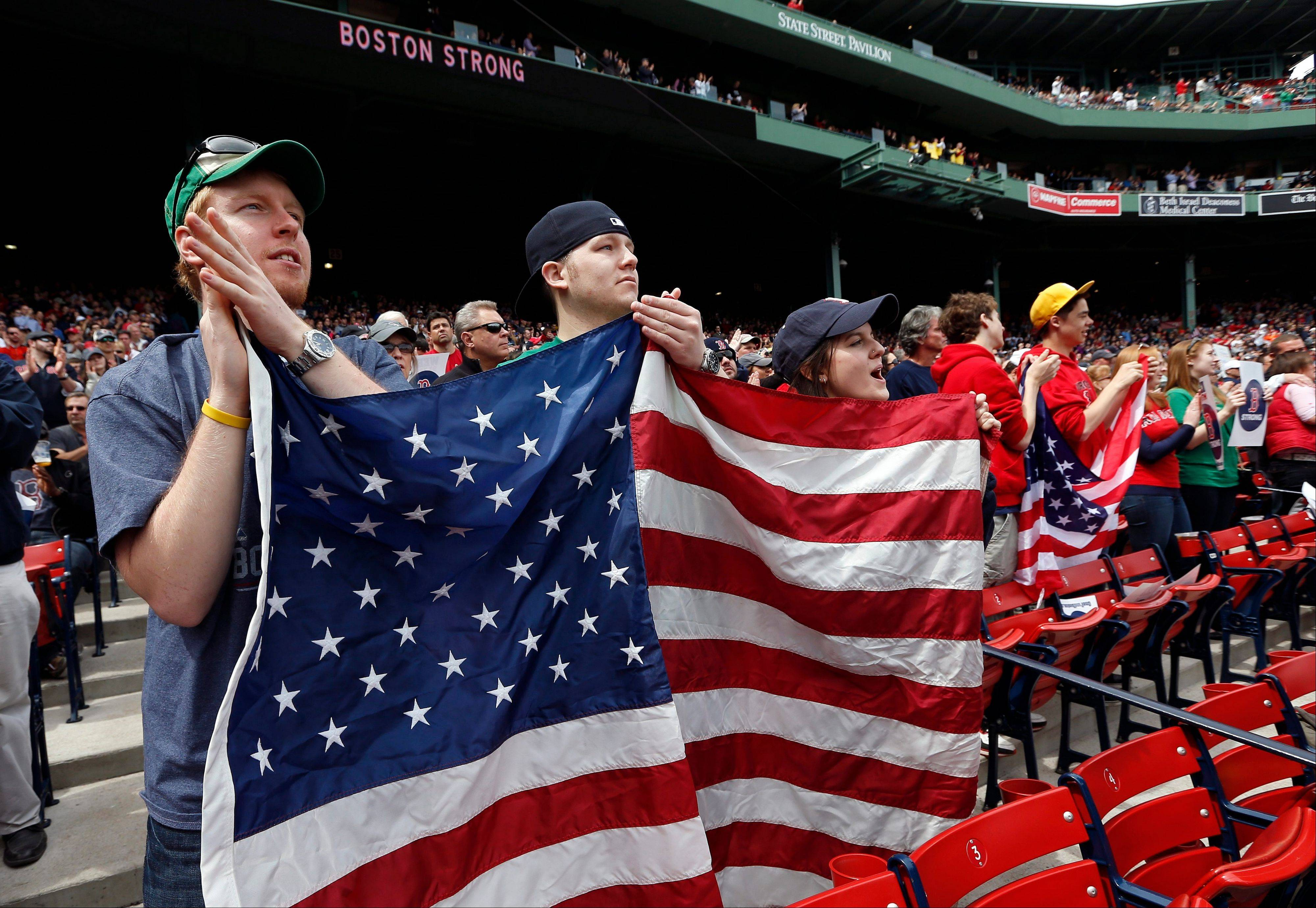 Fans hold an American flag during ceremonies in tribute of victims and first responders to the Boston Marathon bombings before a baseball game between the Boston Red Sox and the Kansas City Royals in Boston, Saturday, April 20, 2013.