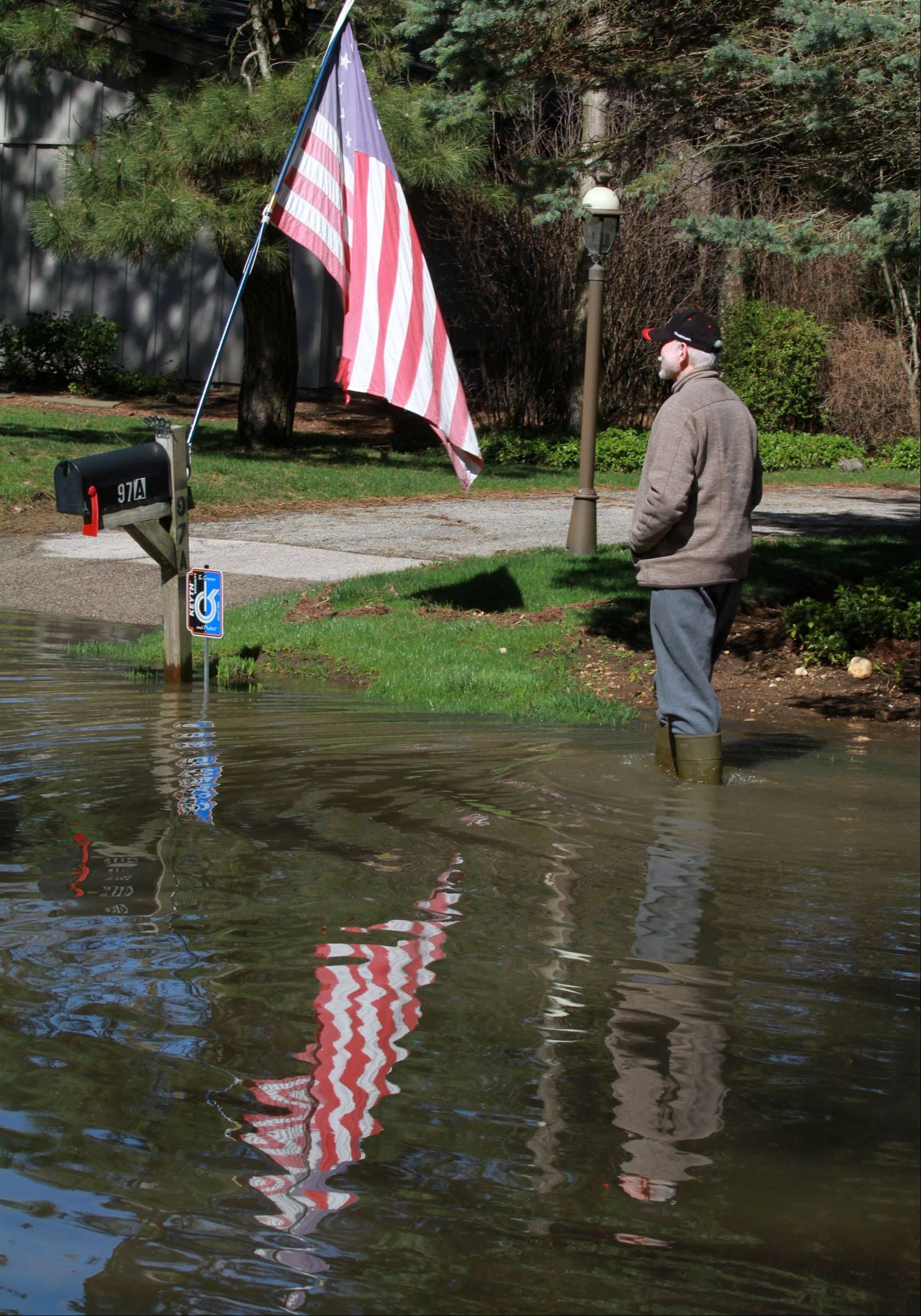 George LeClaire/gleclaire@dailyherald.com Rich Sanders walks back to his house on Lincolnshire Way in Lincolnshire after checking the water level at the end of the block and turning back on Saturday, April 20, 2013. Rich said his house did not get any water.
