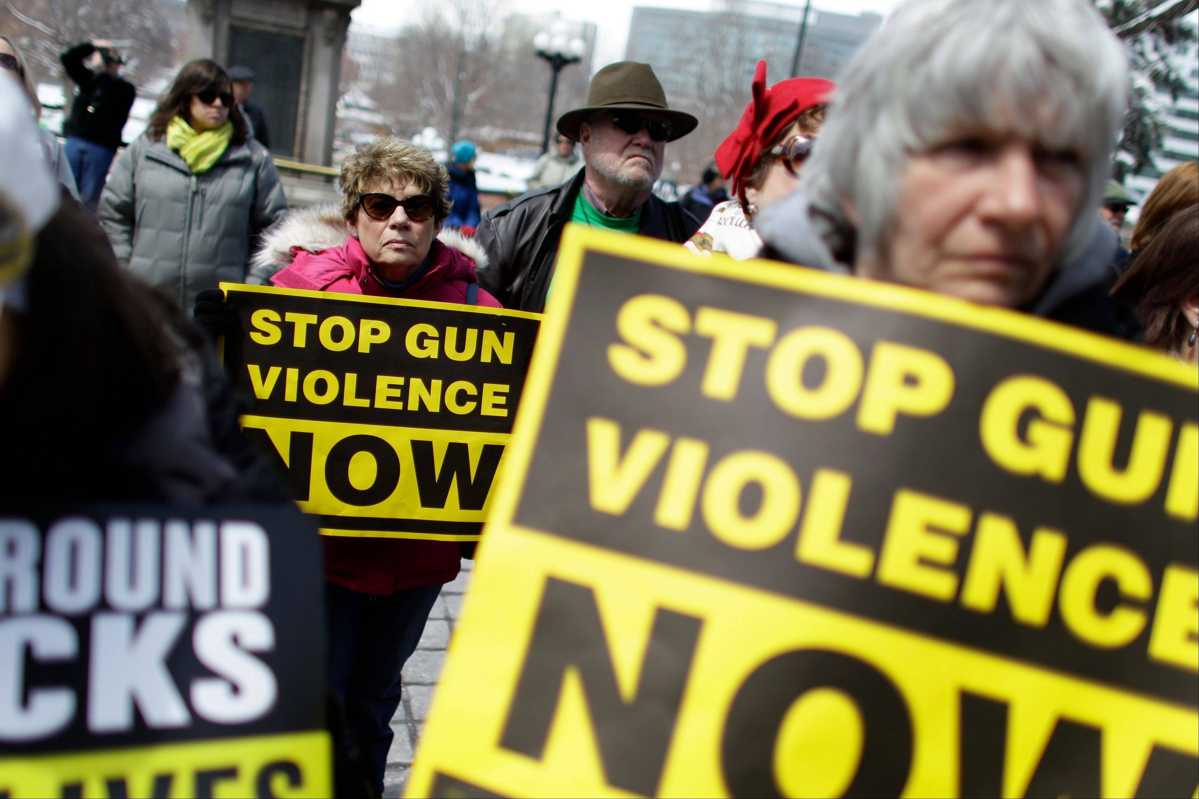 Community gun safety advocates and members of the public hold signs Thursday during a rally and vigil to honor victims of gun violence, sponsored by Colorado Ceasefire, on the steps of the Colorado State Capitol, in Denver.