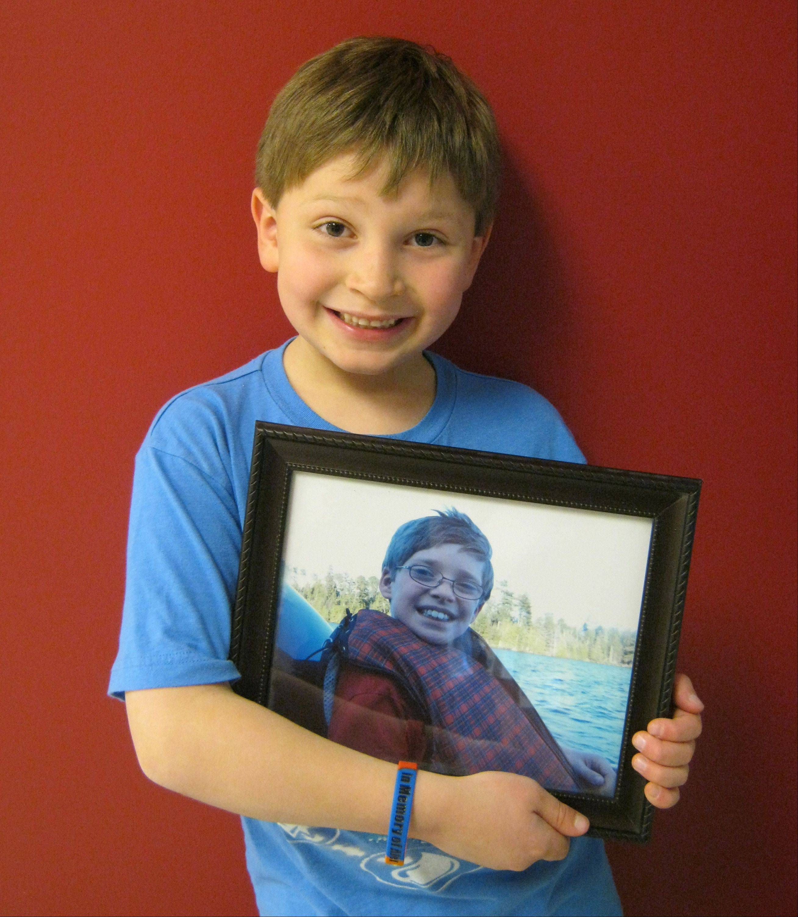Mason Lancaster holds a picture of his brother, Alex, and wears a wristband that first-graders at Big Hollow Primary School in Ingleside are selling to raise money for a scholarship fund. The fund honors Alex, who died last year.