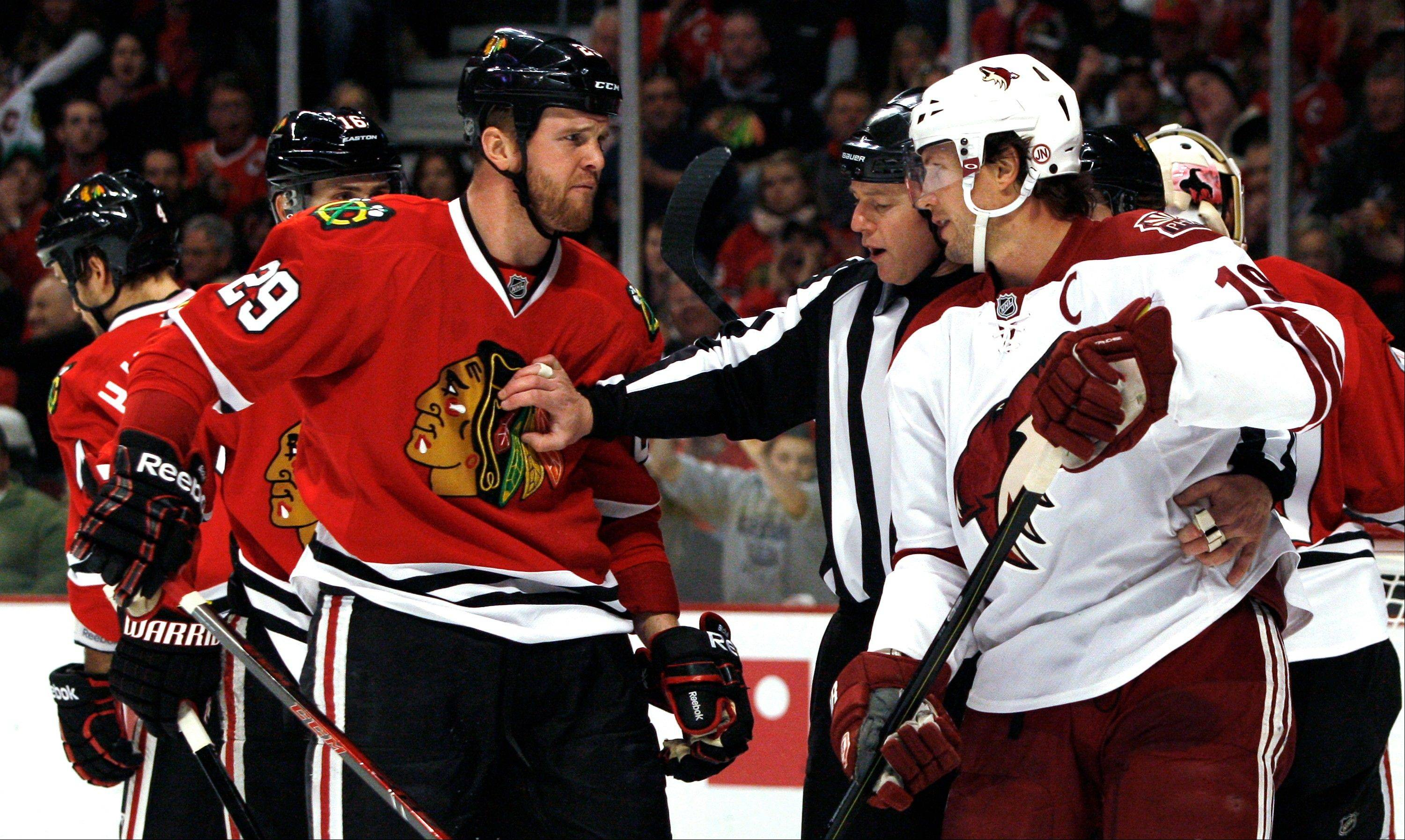 An official separates the Blackhawks� Bryan Bickell, left, and Phoenix Coyotes� Shane Doan during the first period of Saturday�s game in Chicago.