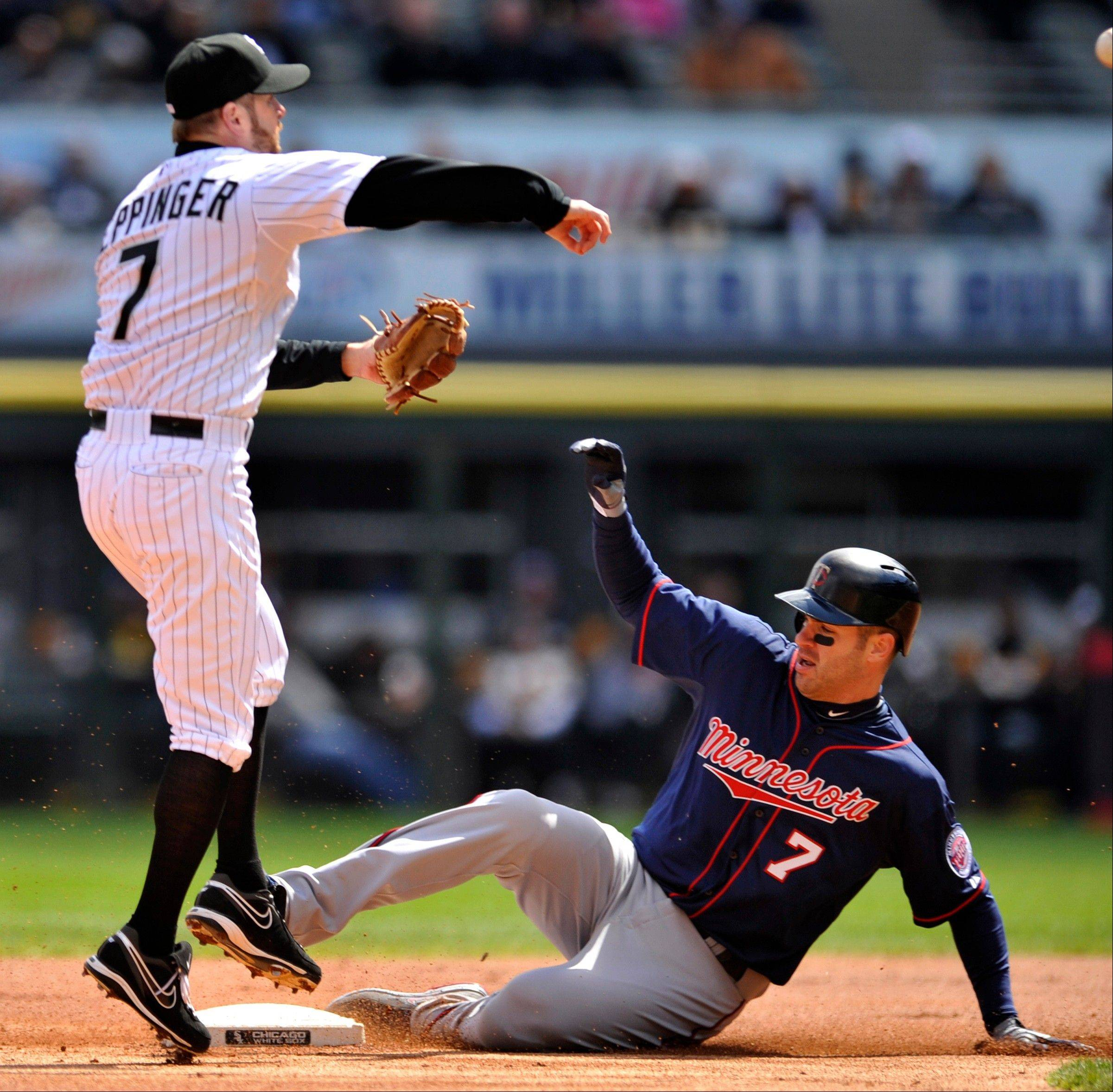 Chicago White Sox second baseman Jeff Keppinger left, watches his throw to first base after forcing out Minnesota Twins' Joe Mauer at second base during the first inning of a baseball game in Chicago, Saturday, April 20, 2013. The Twins' Josh Willingham was safe at first. (AP Photo/Paul Beaty)