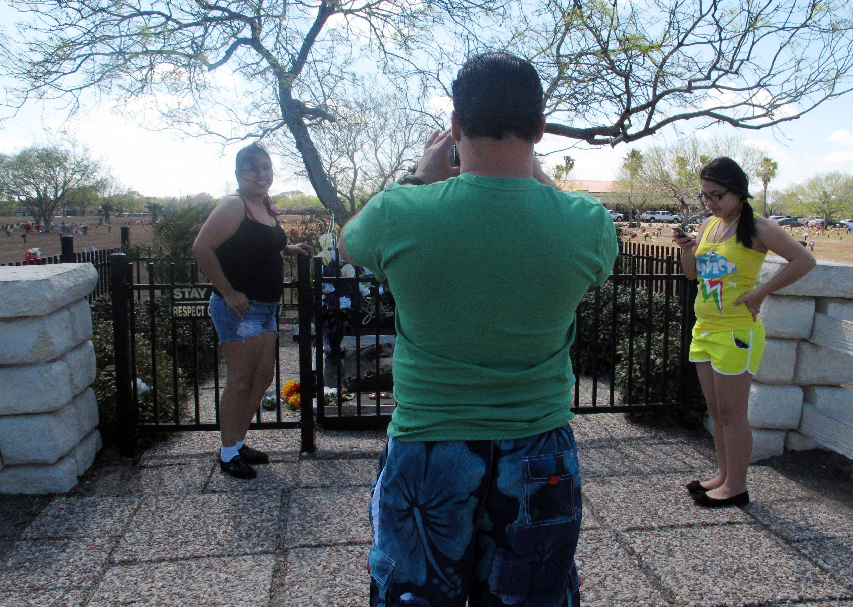 Tourists take photos in front of the resting place of the late Tejano singer, Selena at the Seaside Memorial Park.