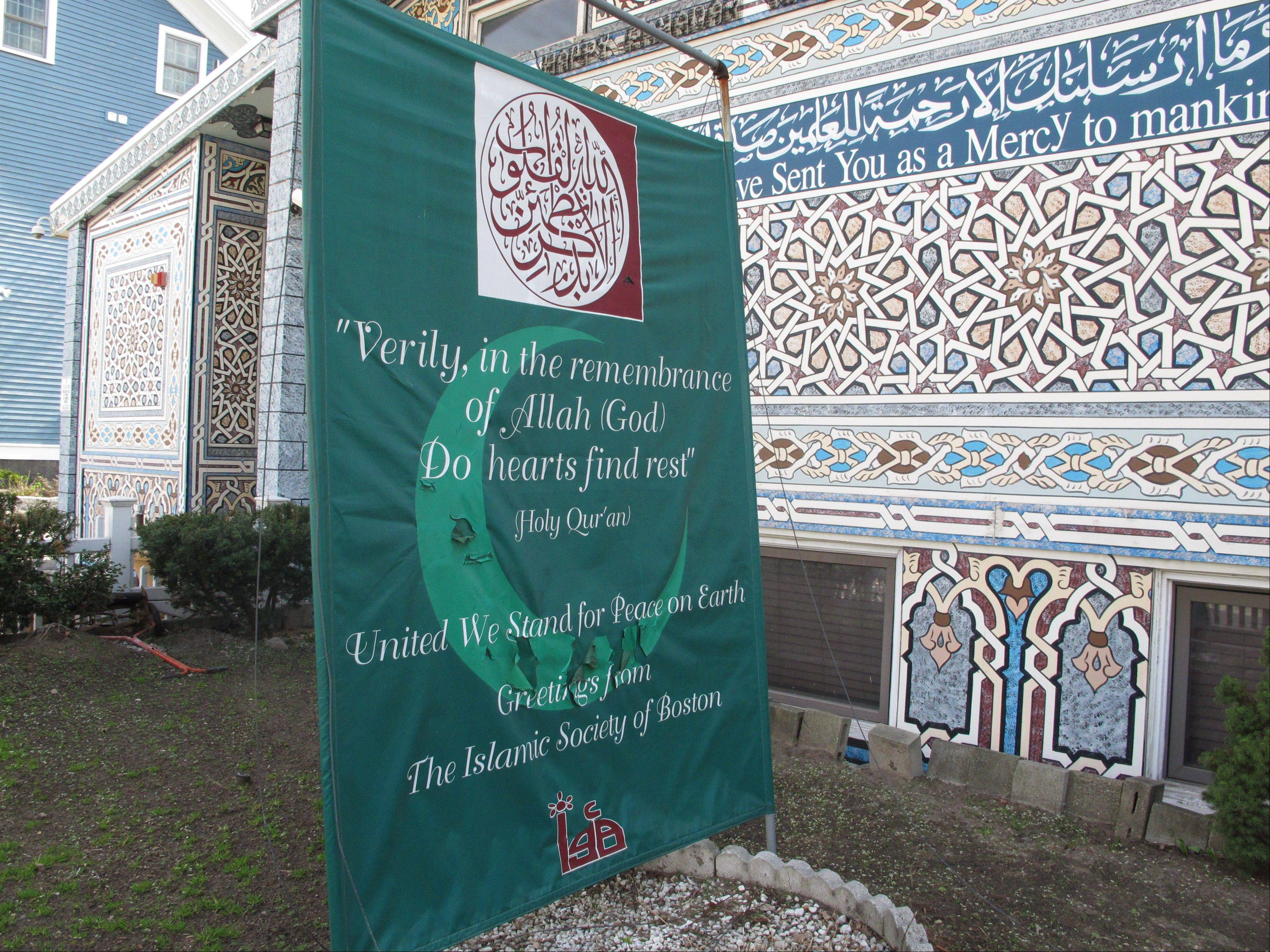 "A banner reading ""United We Stand For Peace on Earth"" stands Friday outside the Islamic Society of Boston mosque in Cambridge, Mass. A mosque official confirmed that the two suspects in the Boston Marathon bombings, who lived a short distance away, worshipped there occasionally."