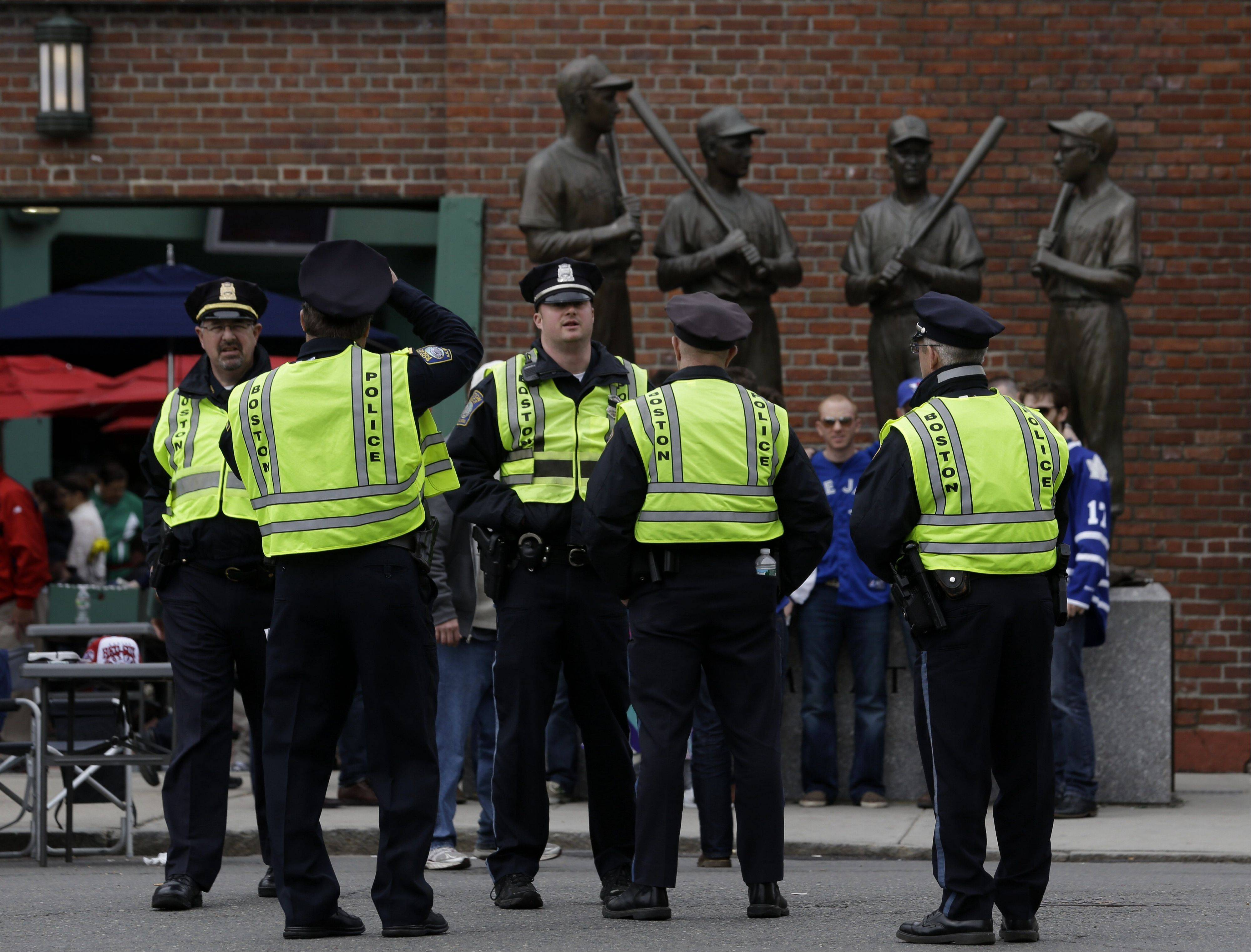Police officers stand near statues of fromer Boston Red Sox greats, from left, Ted Williams, Bobby Doerr, Johnny Pesky and Dom DiMaggio during a baseball game between the Kansas City Royals and the Boston Red Sox, the first game held in the city following the Boston Marathon explosions, Saturday, April 20, 2013, in Boston. Police captured Dzhokhar Tsarnaev, 19, the surviving Boston Marathon bombing suspect, late Friday, after a wild car chase and gun battle earlier in the day left his