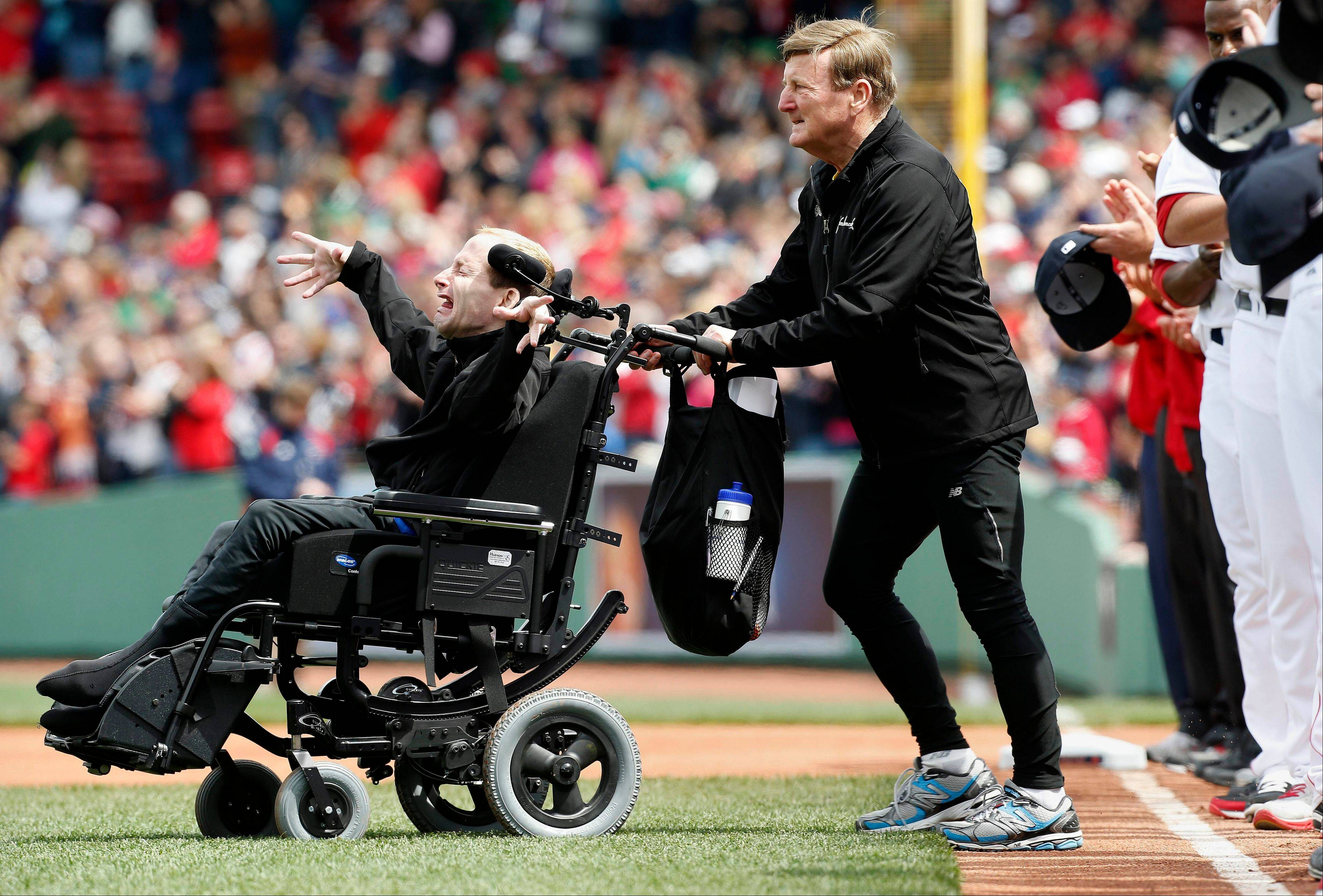 Marathoners Dick Hoyt, right, and his son Rick come onto the field for the ceremonial first pitch before a baseball game between the Boston Red Sox and the Kansas City Royals in Boston, Saturday, April 20, 2013. Playing at home for the first time since two explosions at the Boston Marathon finish line killed three people and wounded more than 180 others, the Red Sox honored the victims and the survivors with a pregame ceremony and an emotional video of scenes from Monday's race.