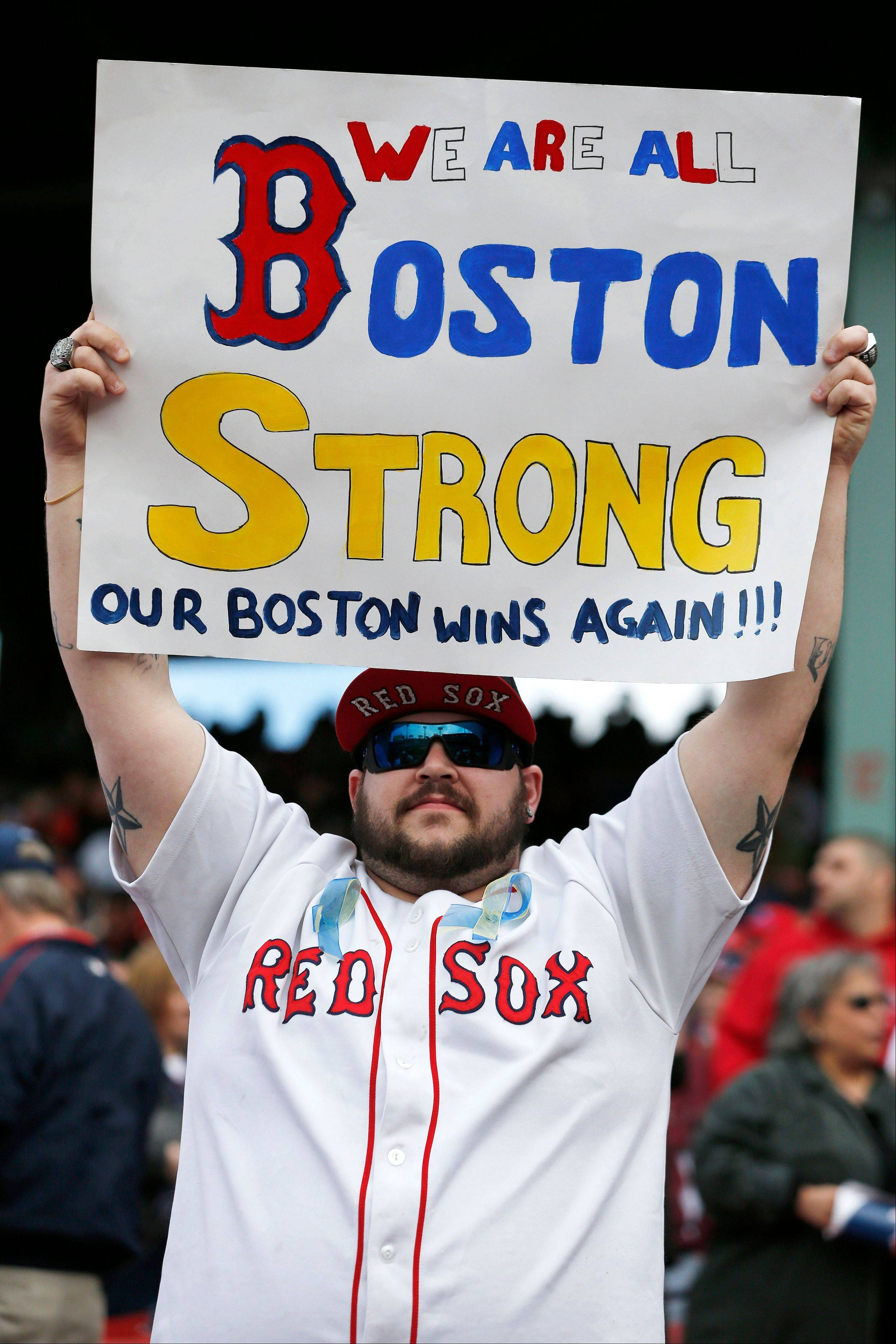 "A fan holds a ""Boston Strong"" sign after the Boston Red Sox defeated the Kansas City Royals 4-3 in a baseball game in Boston, Saturday, April 20, 2013. Playing at home for the first time since two explosions at the Boston Marathon finish line killed three people and wounded more than 180 others, the Red Sox honored the victims and the survivors with a pregame ceremony and an emotional video of scenes from Monday's race."