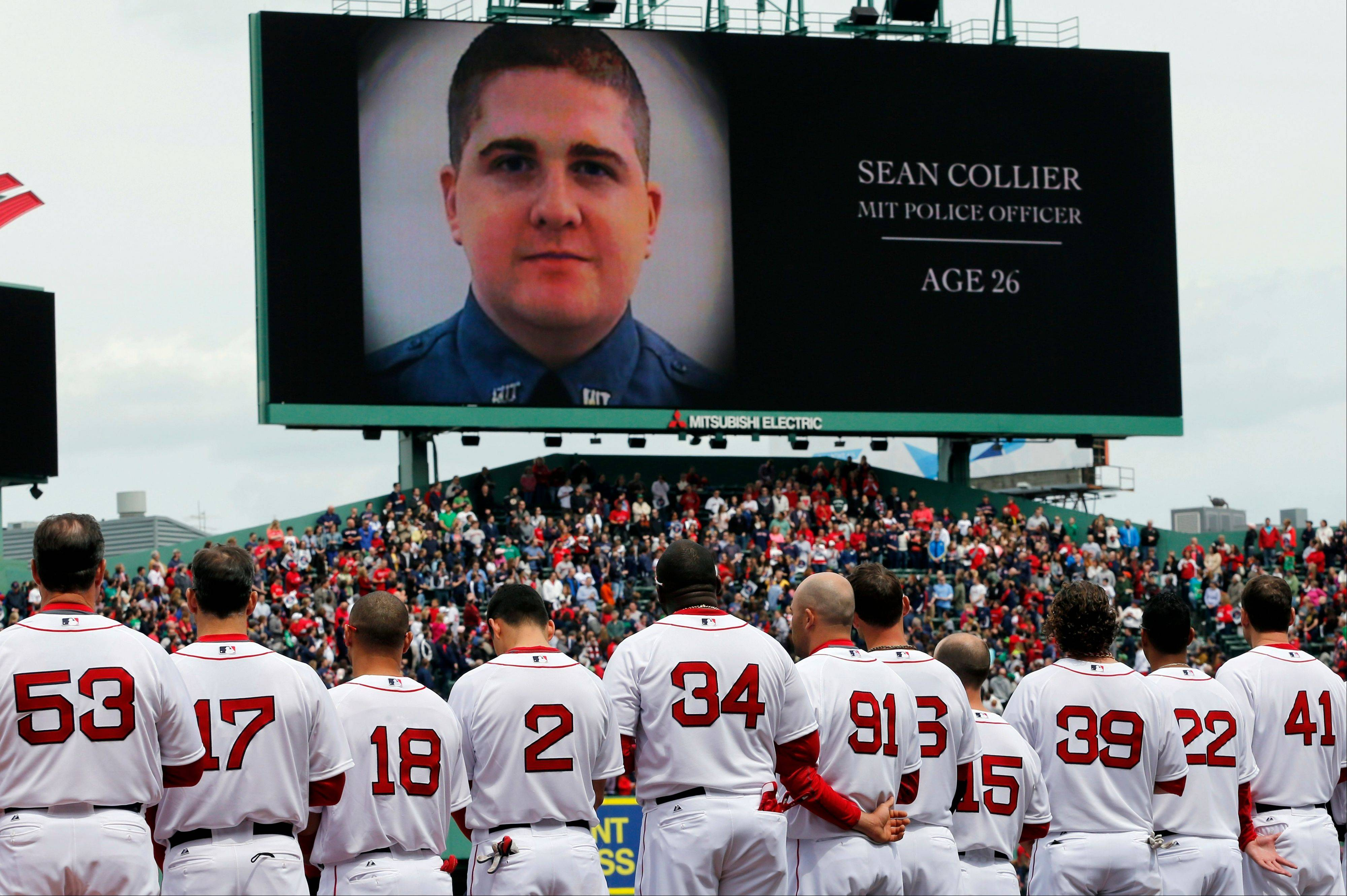 The Boston Red Sox line up during a tribute to victims of the Boston Marathon bombing and its aftermath, as an image of Massachusetts Institute of Technology Police Officer Sean Collier is displayed on the scoreboard, before a baseball game against the Kansas City Royals in Boston, Saturday, April 20, 2013.