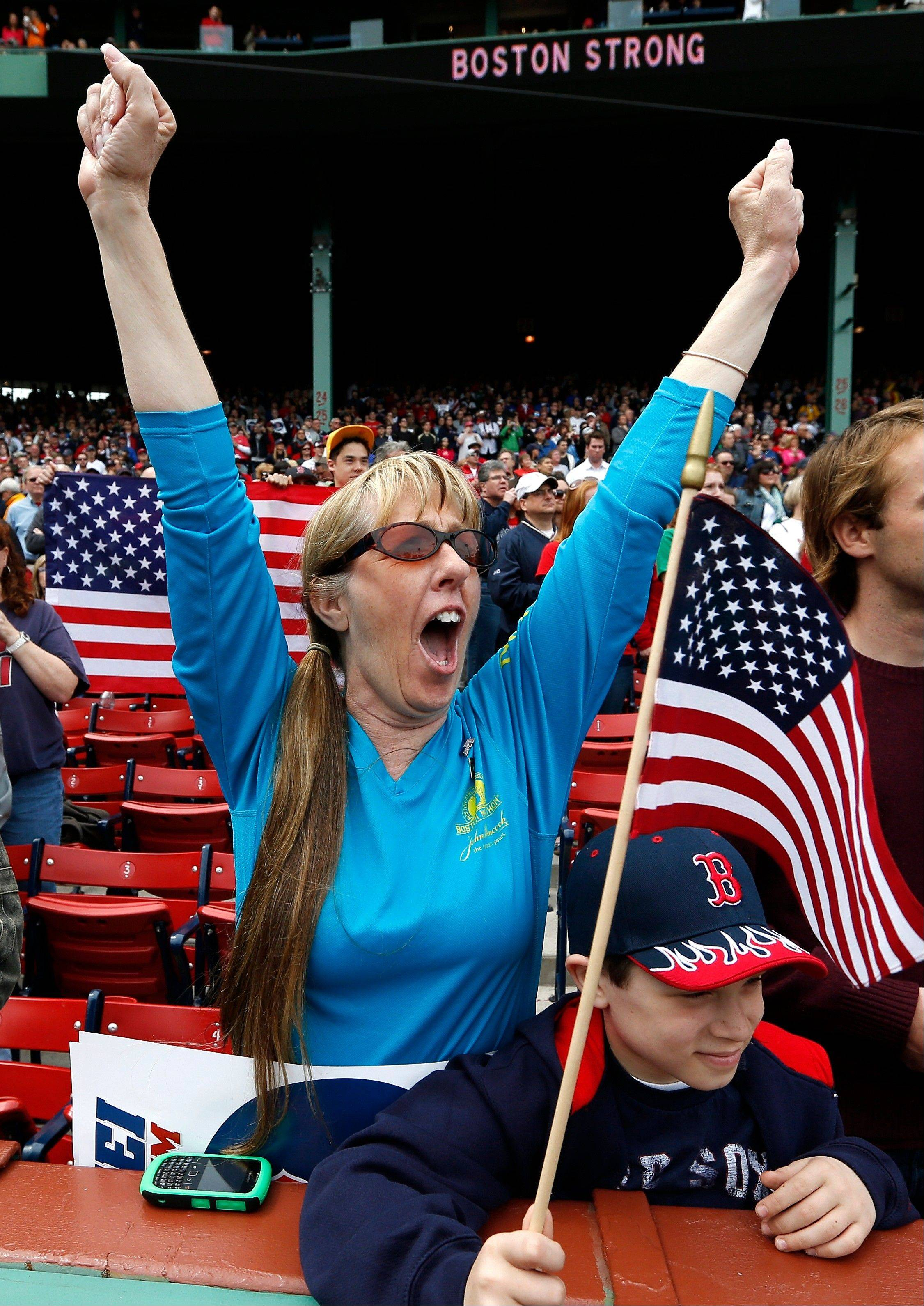 A fan cheers during a tribute to first responders to the Boston Marathon bombing before a baseball game between the Boston Red Sox and the Kansas City Royals in Boston, Saturday, April 20, 2013.
