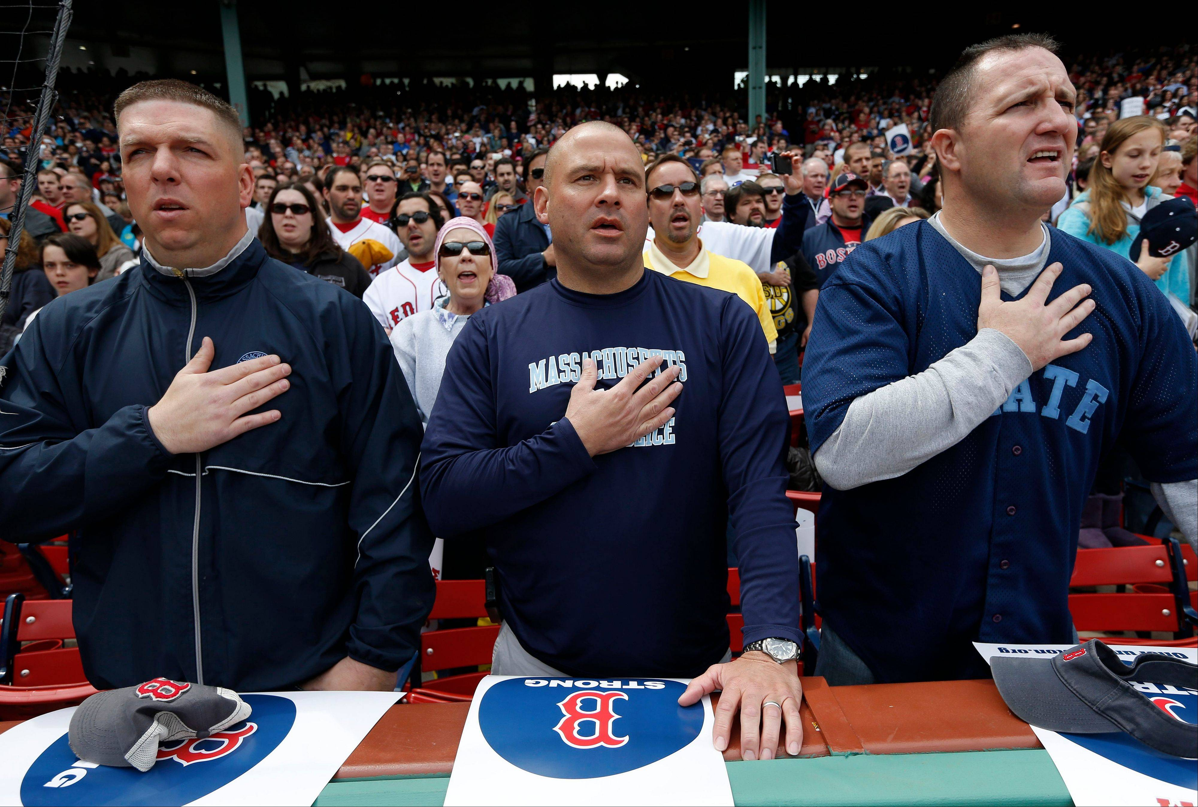 Three members of the Massachusetts State Police place their hands over their heart during the national anthem before a baseball game between the Boston Red Sox and the Kansas City Royals in Boston, Saturday, April 20, 2013.