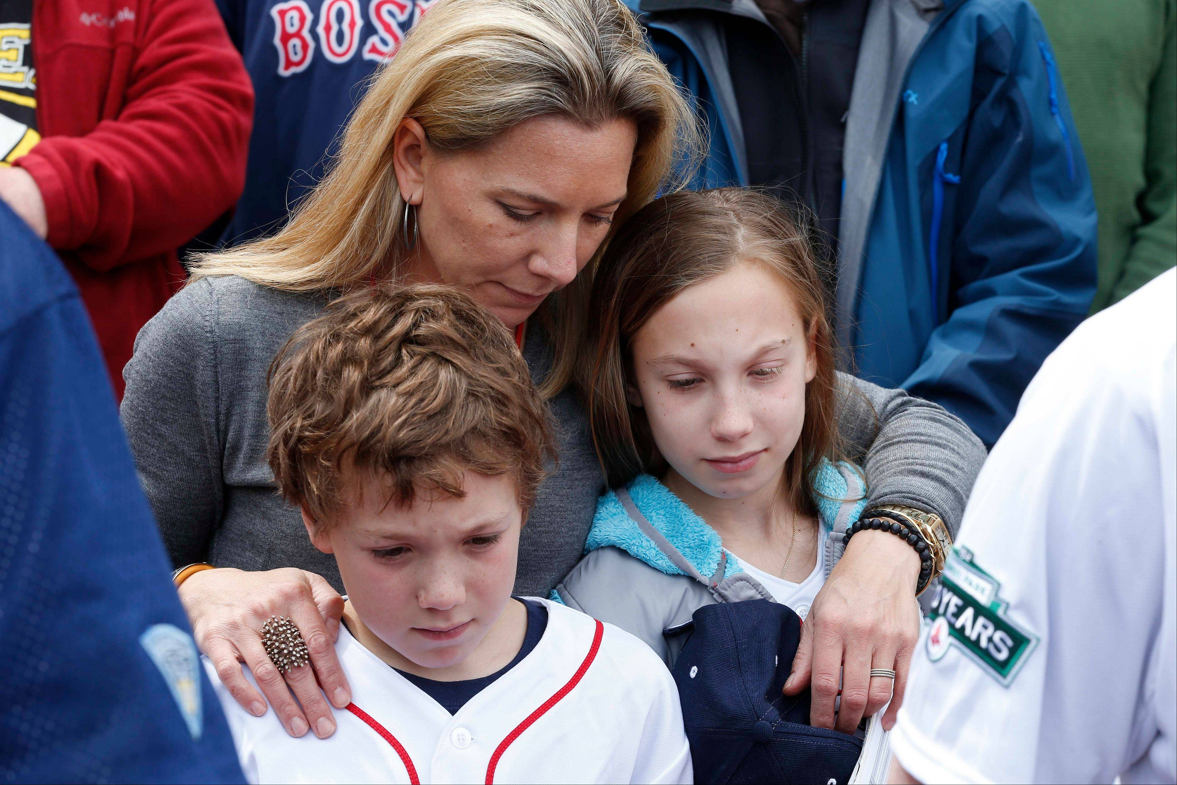 A woman bows her head between two children during a moment of silence for the victims of the Boston Marathon bombings, before a baseball game between the Boston Red Sox and the Kansas City Royals in Boston, Saturday, April 20, 2013.