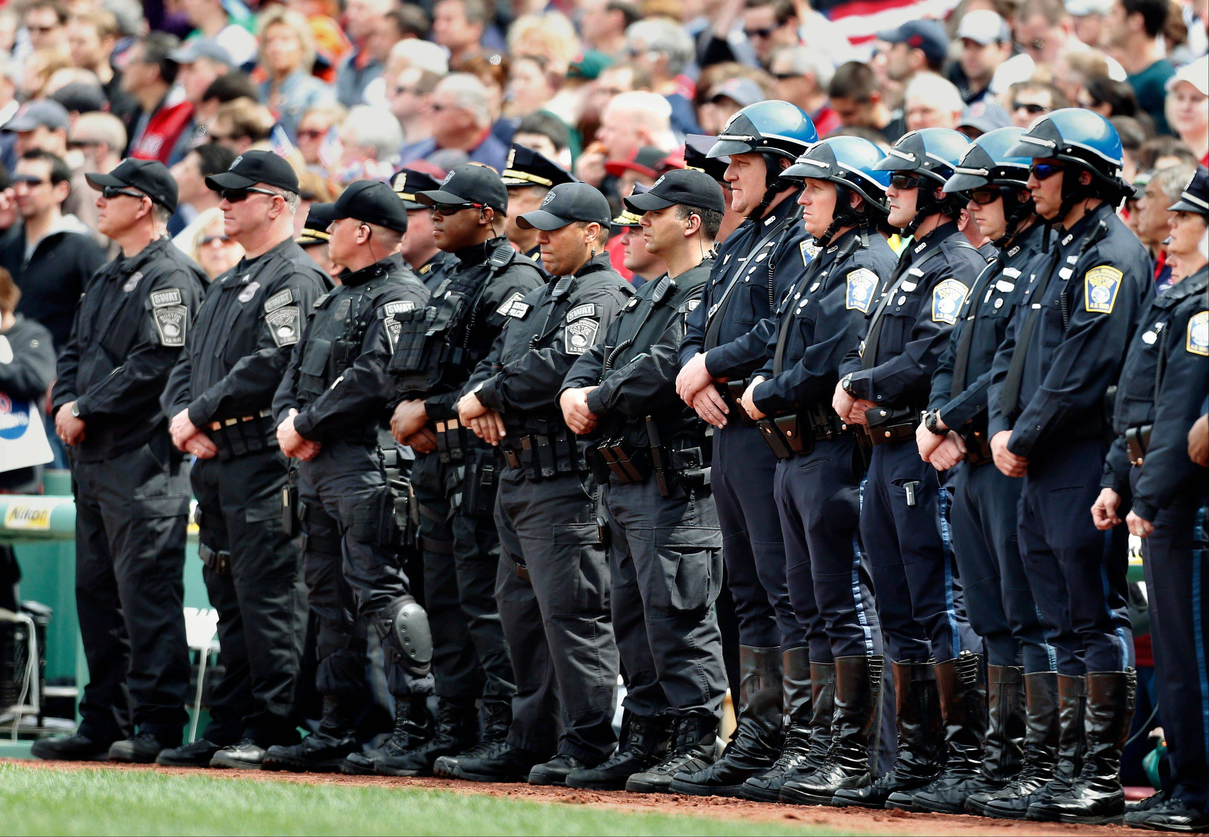 Boston police personnel stand on the field during ceremonies in honor of victims of and first responders to the Boston Marathon bombings, before a baseball game between the Boston Red Sox and the Kansas City Royals in Boston, Saturday, April 20, 2013.
