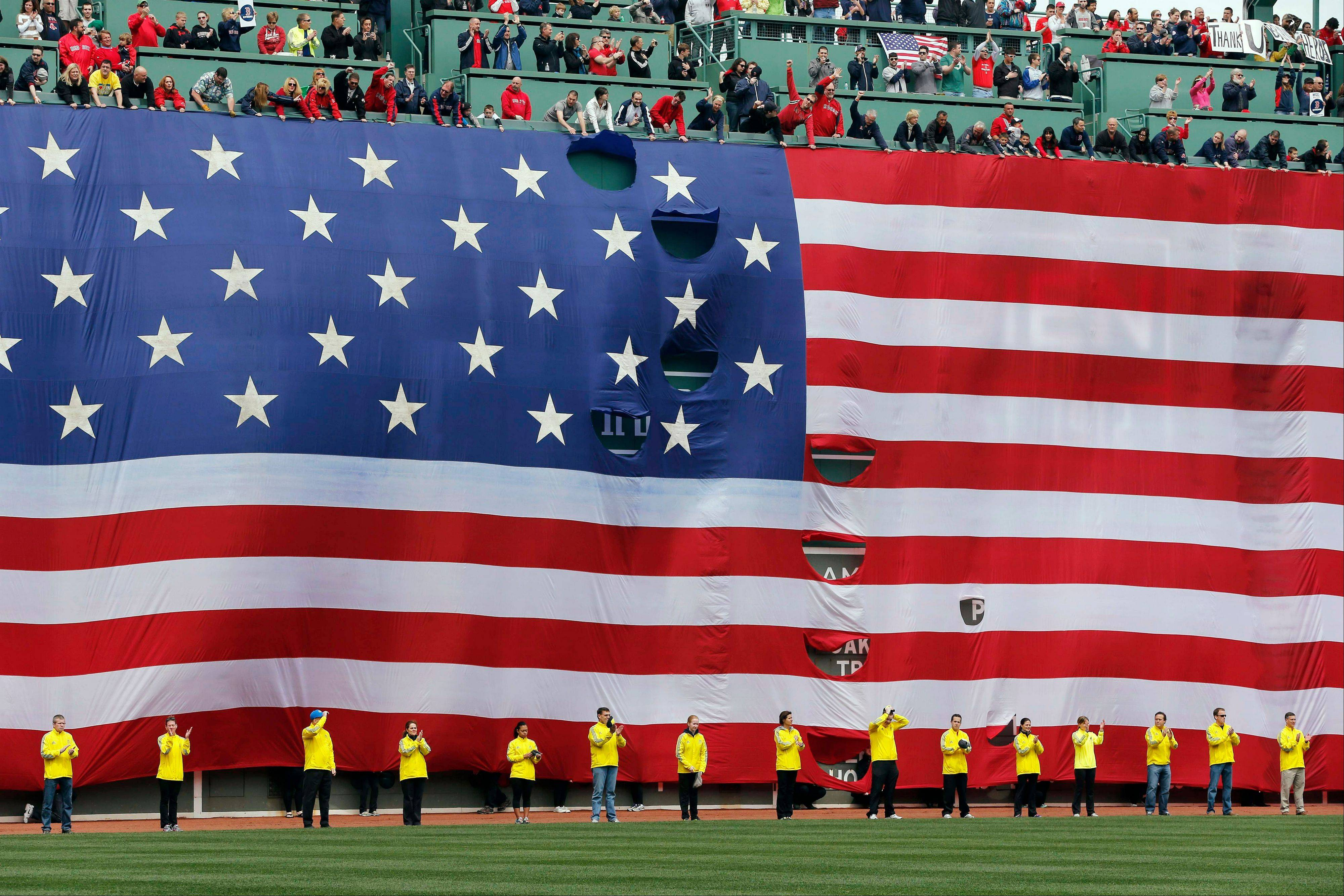 Boston Marathon volunteers stand beneath a giant flag on the outfield wall during a tribute to victims of the Boston Marathon bombings, before a baseball game between the Boston Red Sox and the Kansas City Royals in Boston, Saturday, April 20, 2013.