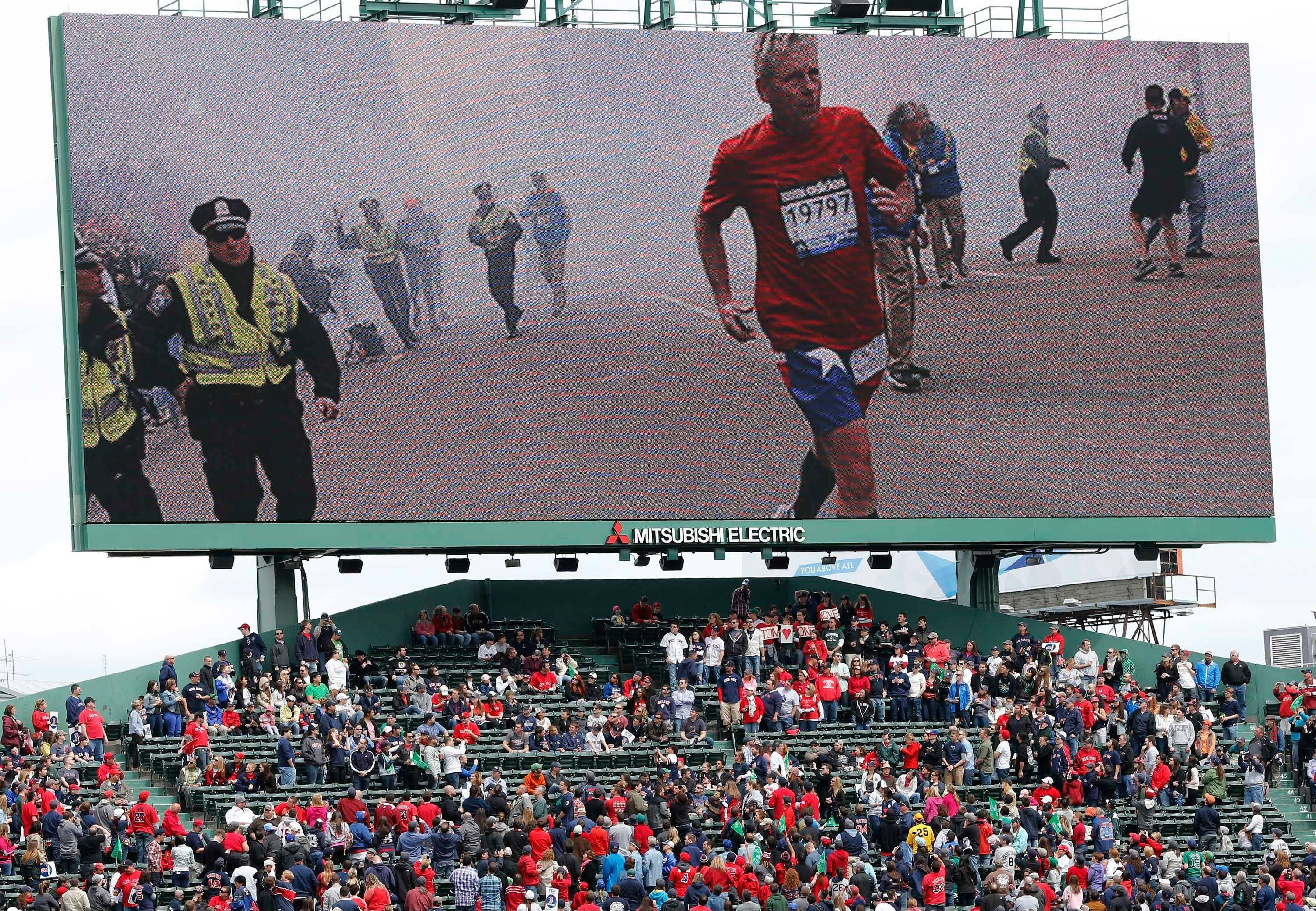 Scenes from the Boston Marathon bombings is displayed on an outfield screen before a baseball game between the Boston Red Sox and the Kansas City Royals in Boston, Saturday, April 20, 2013.