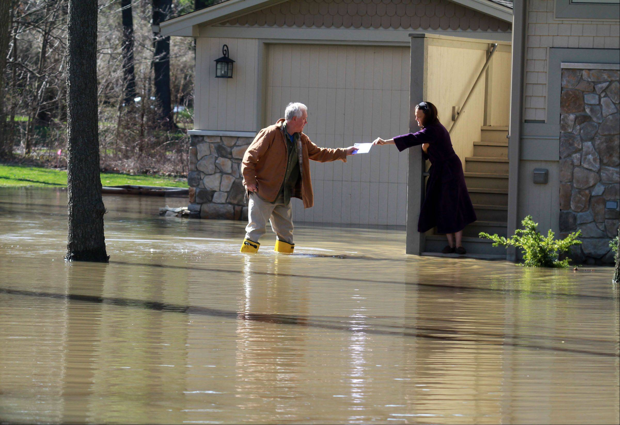 Michelle VanDuynhoven gives her husband, John, a letter to mail at the bottom of the steps to their home on Stonegate Circle in Lincolnshire on Saturday, April 20, 2013. John said there was no water in their house because they rebuilt it higher up in 2010.