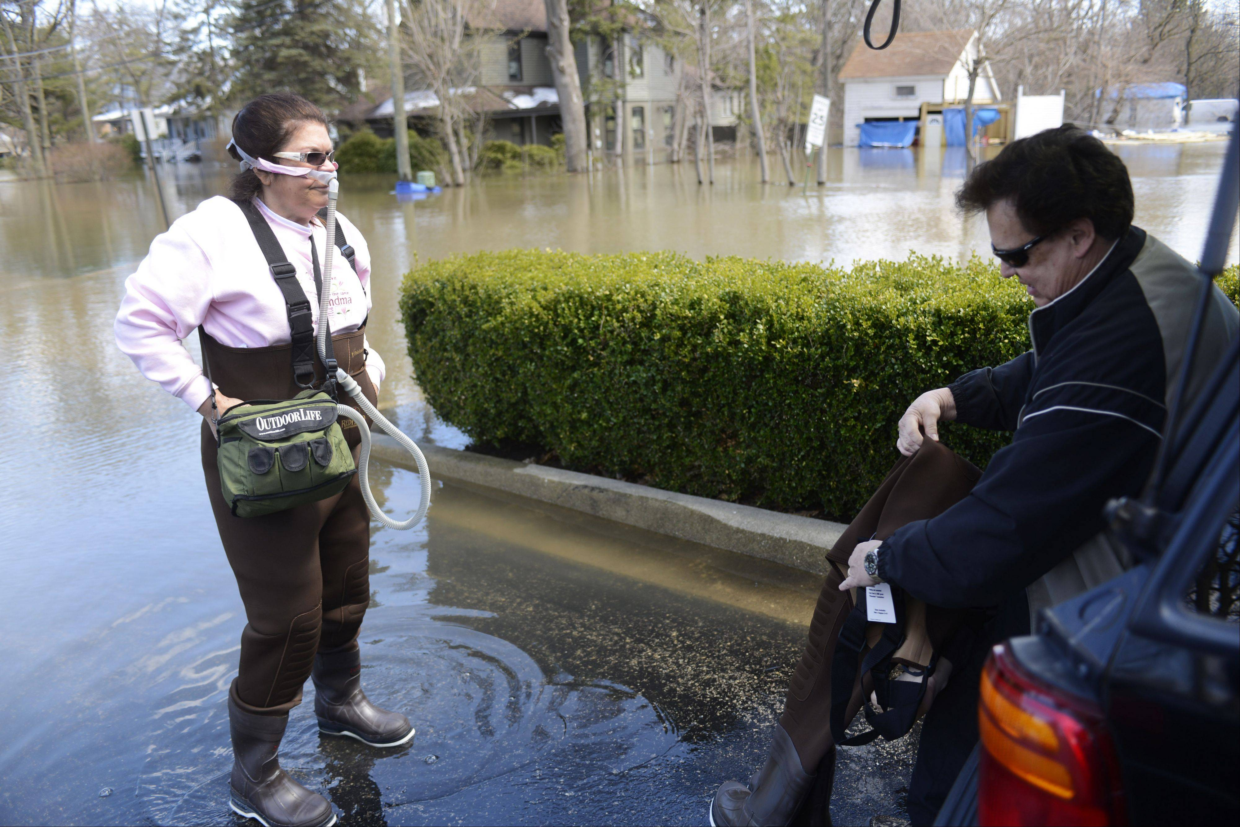 Sherrie Borg, who is afflicted with a chronic, life-threatening lung disease, waits for her husband Walter to get into a set of waders so they can walk to their home on Big Bend in Des Plaines Saturday. The couple had to go all the way to Gurnee to the Bass Pro Shops for the waders.