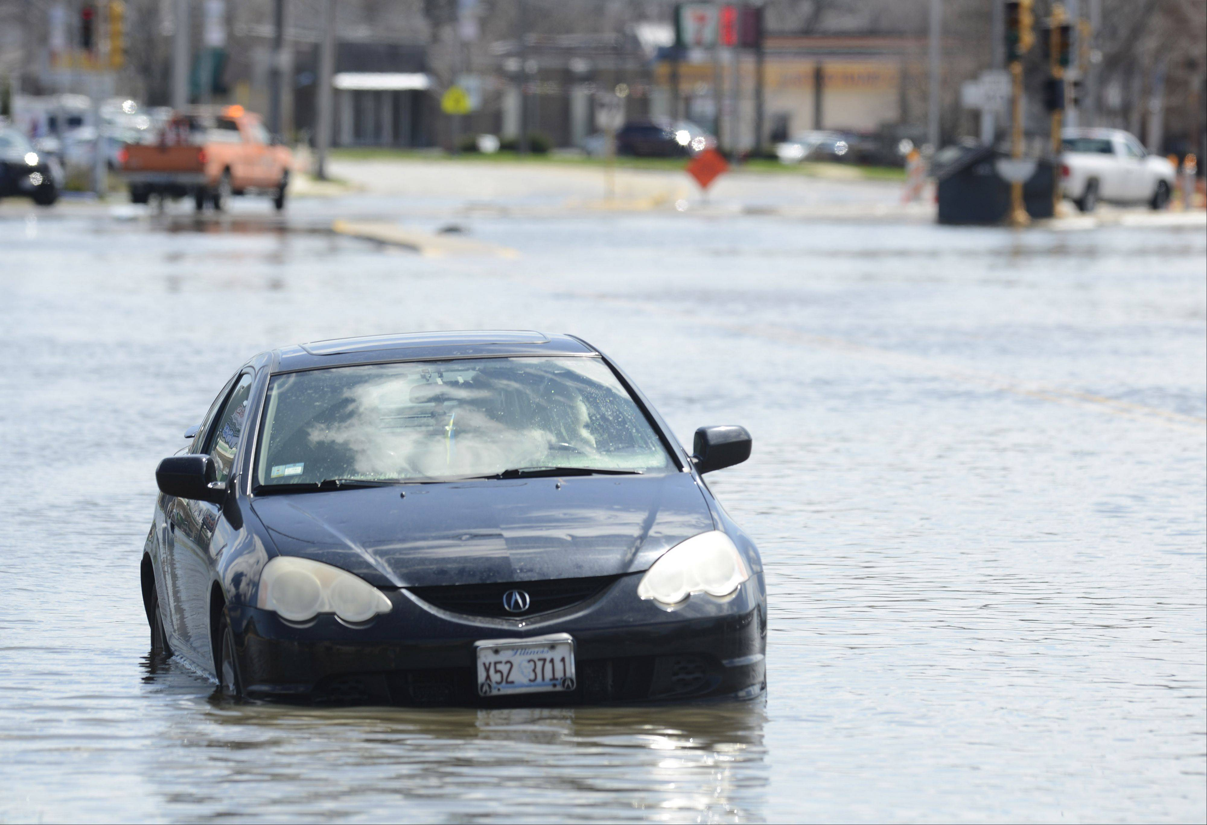 A car is stranded in floodwater on Rand Road just west of River Road in Des Plaines Saturday.