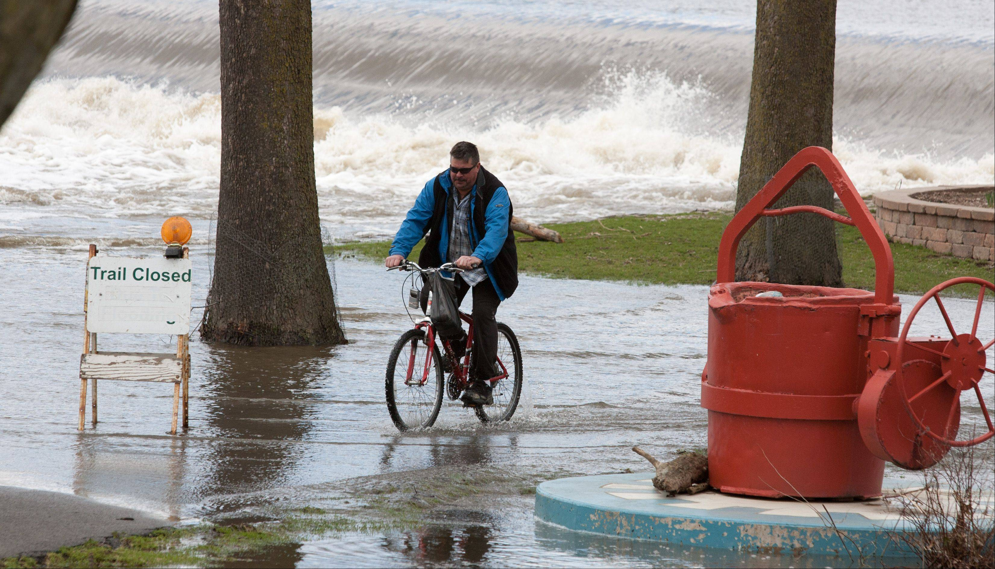 A bike rider weaves through water before a news conference Saturday along the Fox River in North Aurora.