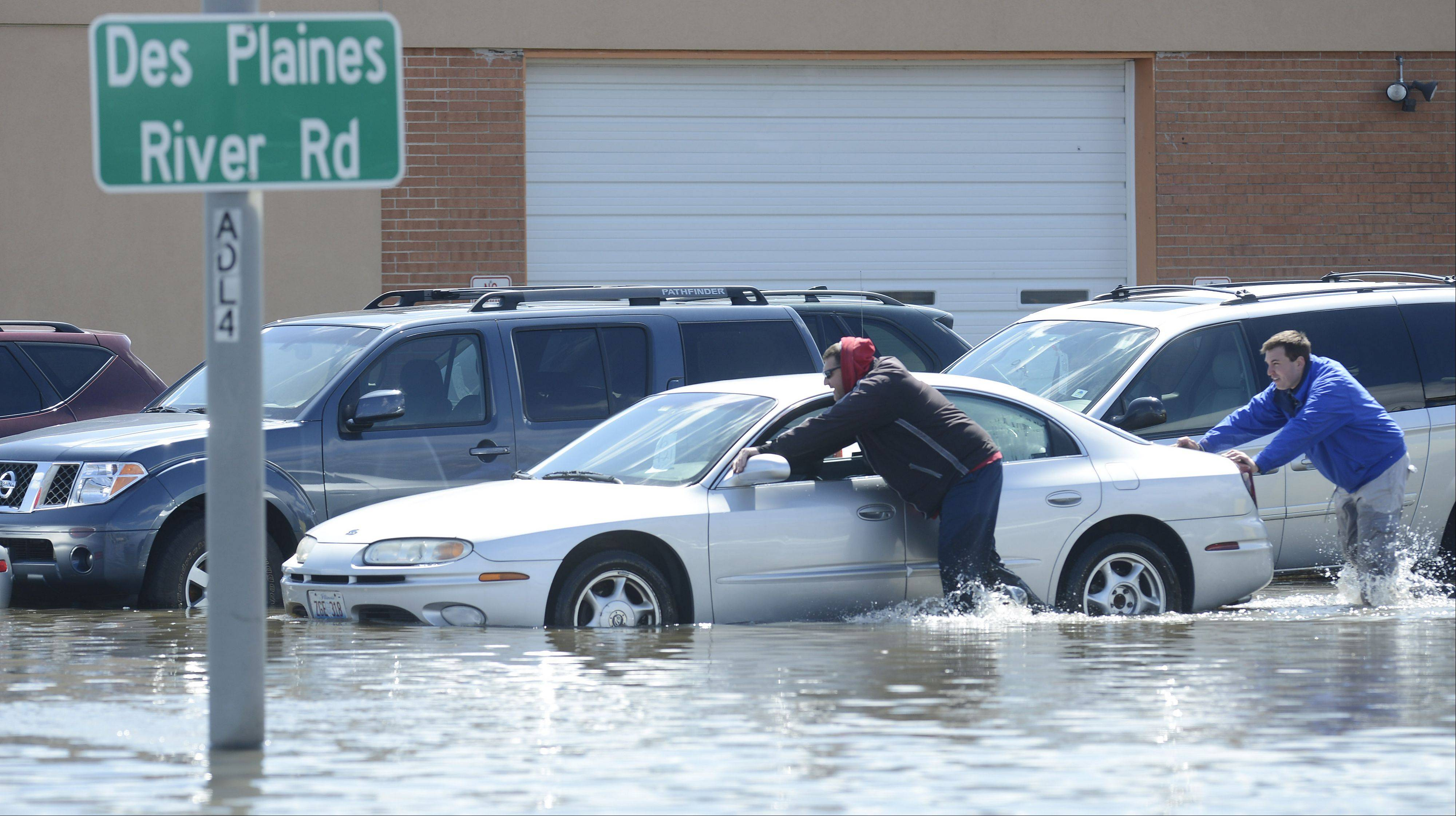 Steve Rush, left, and Rob Burns push a car from a flooded used car lot toward higher ground in Des Plaines Saturday. The pair started the cars once they were safely on higher ground.
