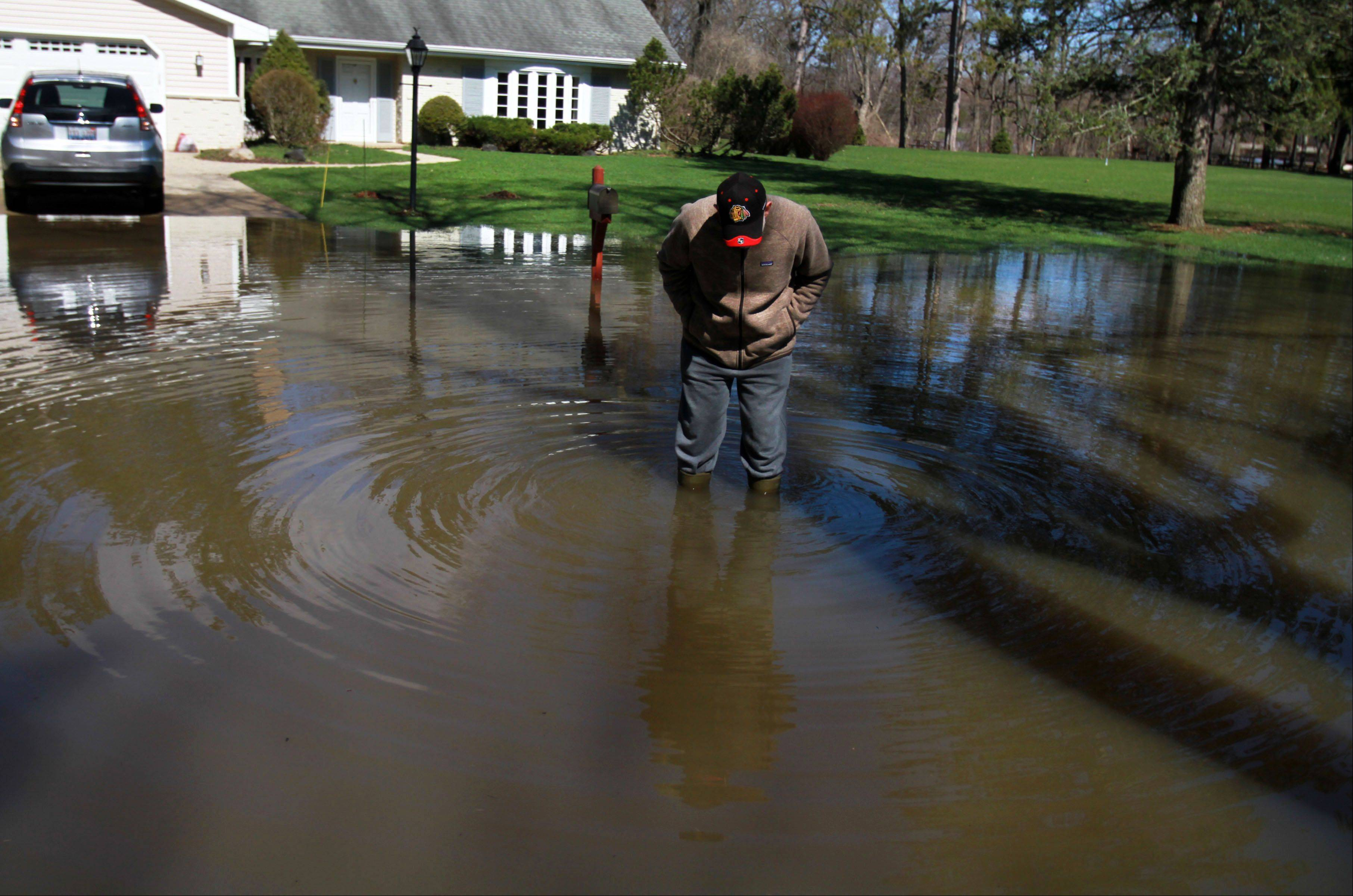 George LeClaire/gleclaire@dailyherald.comRich Sanders checks the level of the water on his boots and decides to walk back to his house on Lincolnshire Way in Lincolnshire. Sanders wanted to checking the water level at the end of the block but turning back on Saturday, April 20, 2013. Rich said his house did not get any water.