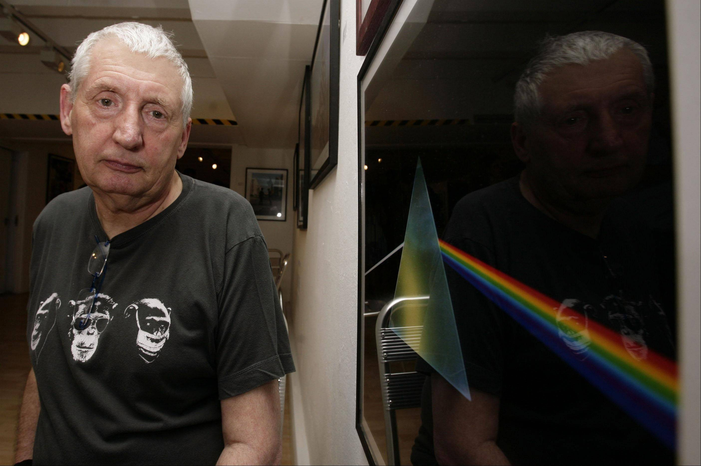 "English graphic designer Storm Thorgerson standing next to his album cover artwork for Pink Floyd's ""The Dark Side of the Moon"" during the opening of his exhibition 'Mind Over Matter: The Images of Pink Floyd' in London."