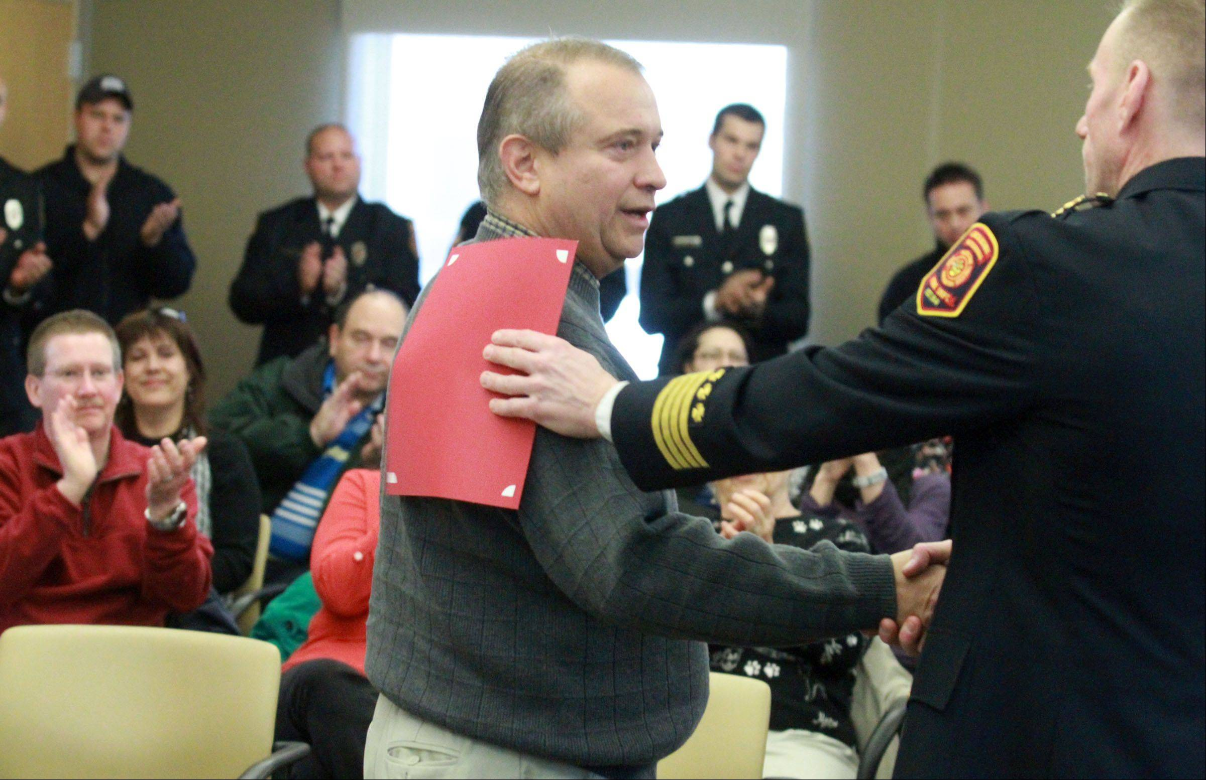 Fernando Meir, a Stevenson High School employee, is recognized Saturday by Deputy Chief Tom Krueger for saving a family trapped in a fire at a home on Apple Hill Lane in unincorporated Lake County near Lincolnshire.
