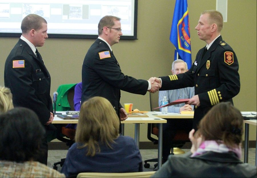 Firefighters John McWilliams, from left, and Ryan Shay are recognized Saturday by Deputy Chief Tom Krueger for saving civilians trapped in a fire at a home on Apple Hill Lane in Prairie View in unincorporated Lake County near Lincolnshire. The presentation was made during a fire district board meeting at Lincolnshire-Riverwoods Fire Protection District Station 53 in Vernon Hills.