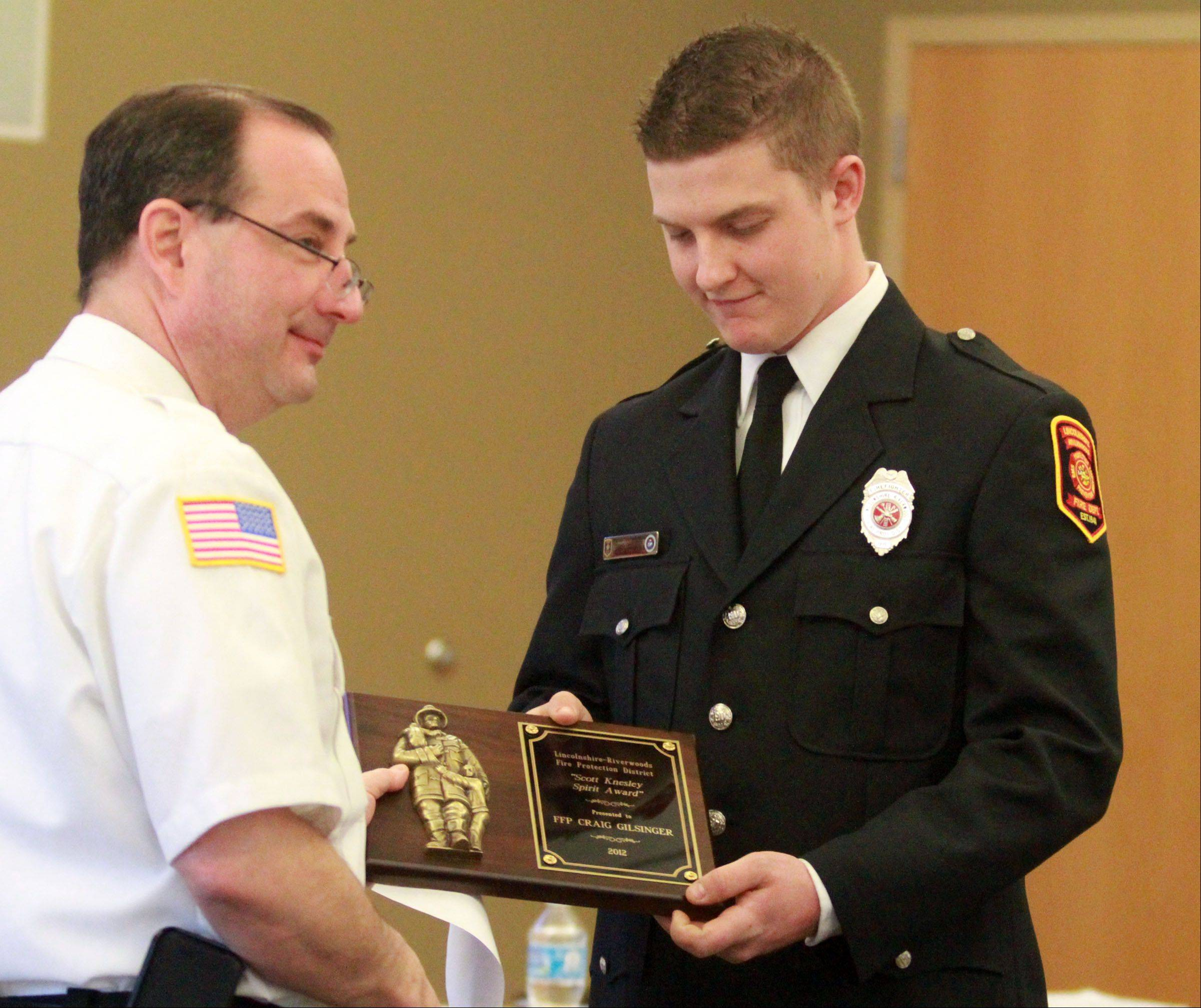Deputy Chief Tony Ugaste, left, of the Lincolnshire-Riverwoods Fire Department presents the department's annual award Saturday to firefighter Craig Gilsinger during a fire district board meeting at Lincolnshire-Riverwoods Fire Protection District Station 53 in Vernon Hills.