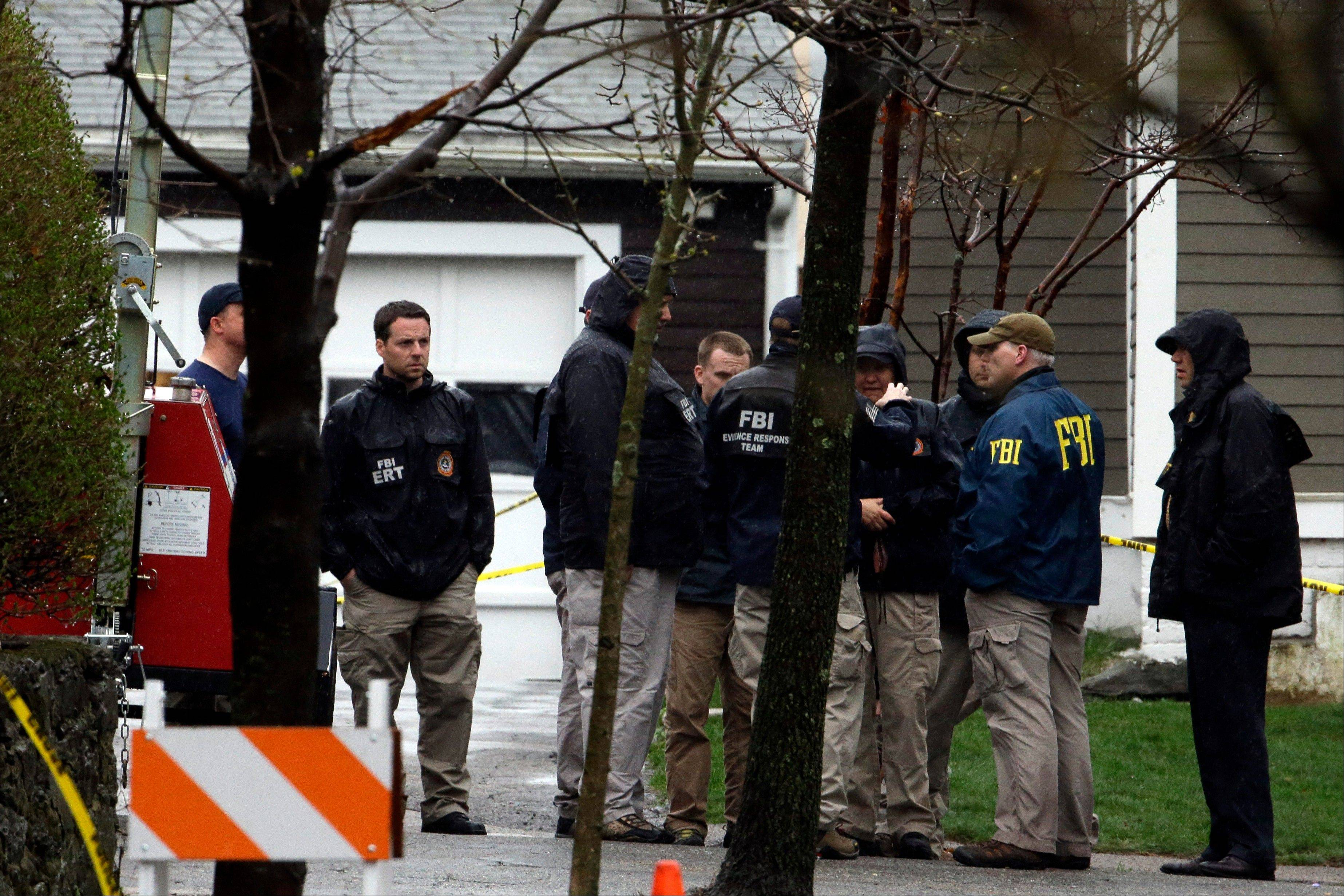 Investigators work near the location where the previous night a suspect in the Boston Marathon bombings was arrested, Saturday, April 20, 2013, in Watertown, Mass. Police captured Dzhokhar Tsarnaev, 19, the surviving Boston Marathon bombing suspect, in a backyard boat after a wild car chase and gun battle that left his older brother dead.