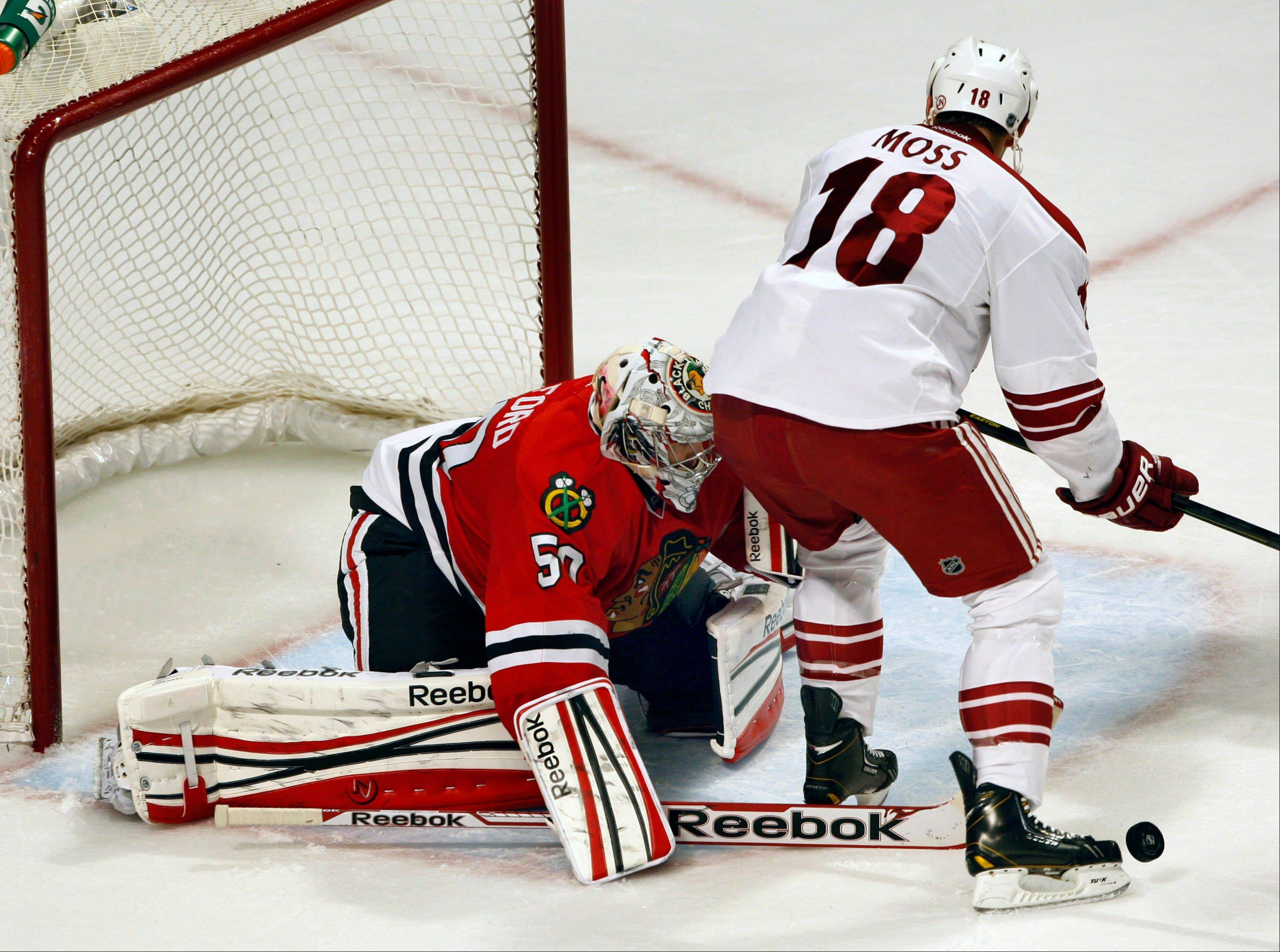 Blackhawks goalie Corey Crawford stops a shot by the Coyotes' David Moss on Saturday night.