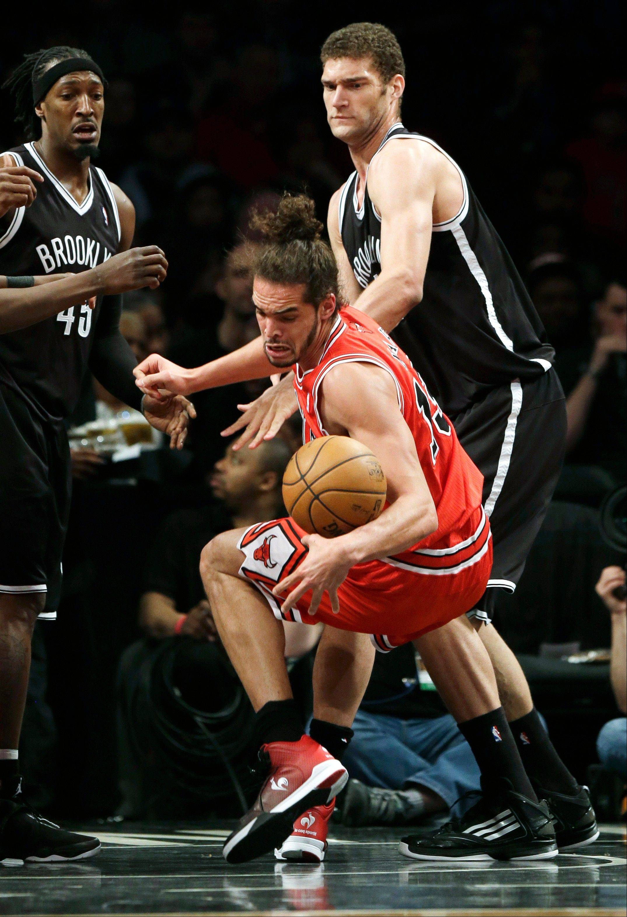 Brooklyn Nets' Brook Lopez, right, fouls the Bulls' Joakim Noah, center, while Nets' Gerald Wallace watches during the second half of Game 1 in a first-round NBA basketball playoff series, Saturday, April 20, 2013 in New York. The Nets beat the Bulls 106-89.