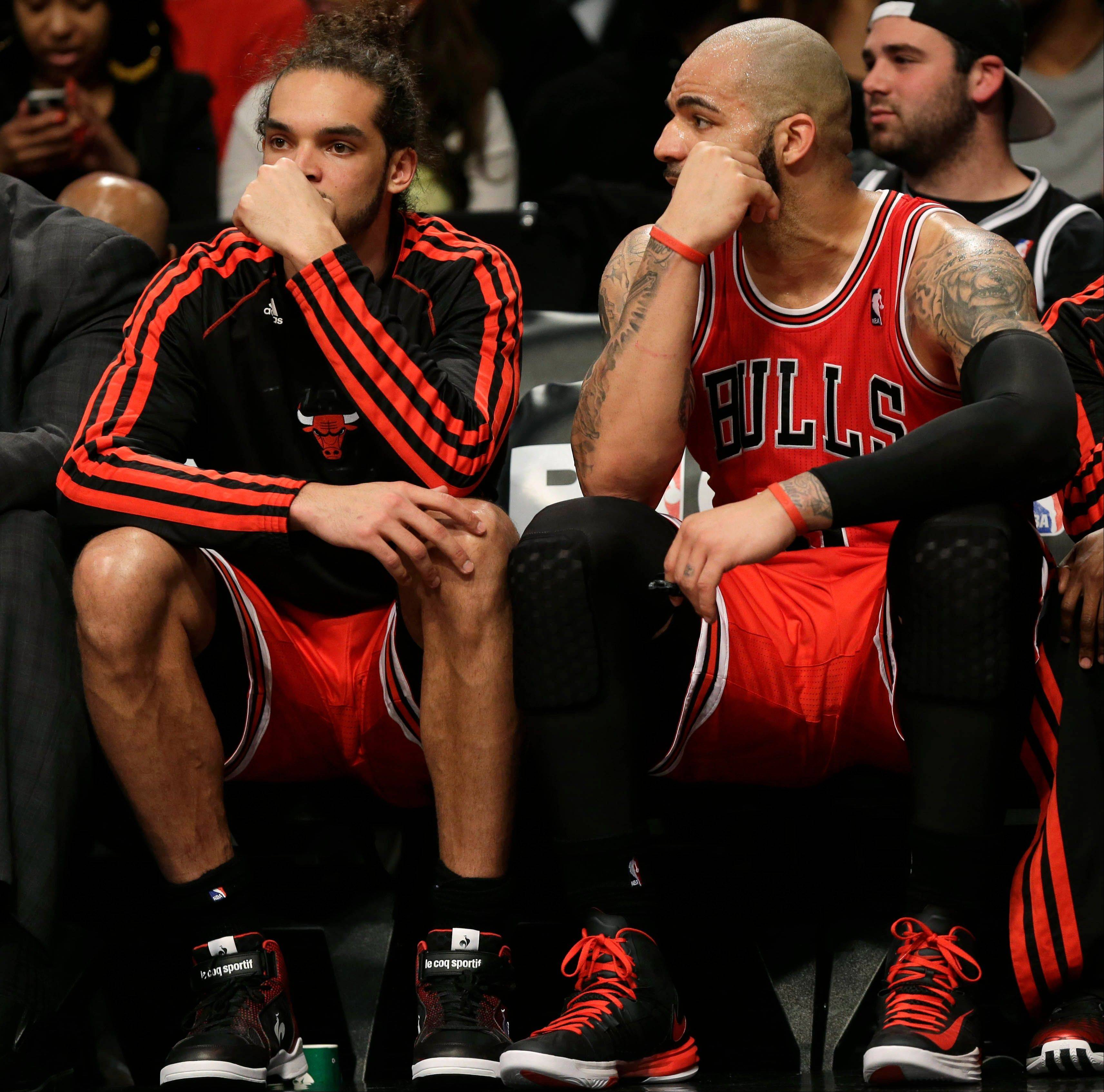 The Bulls' Joakim Noah, left, and Carlos Boozer watch the end of the game against the Brooklyn Nets from the bench during the second half of Game 1 in the first round of the NBA basketball playoffs at the Barclays Center, Saturday, April 20, 2013, in New York. The Nets defeated the Bulls 106-89.