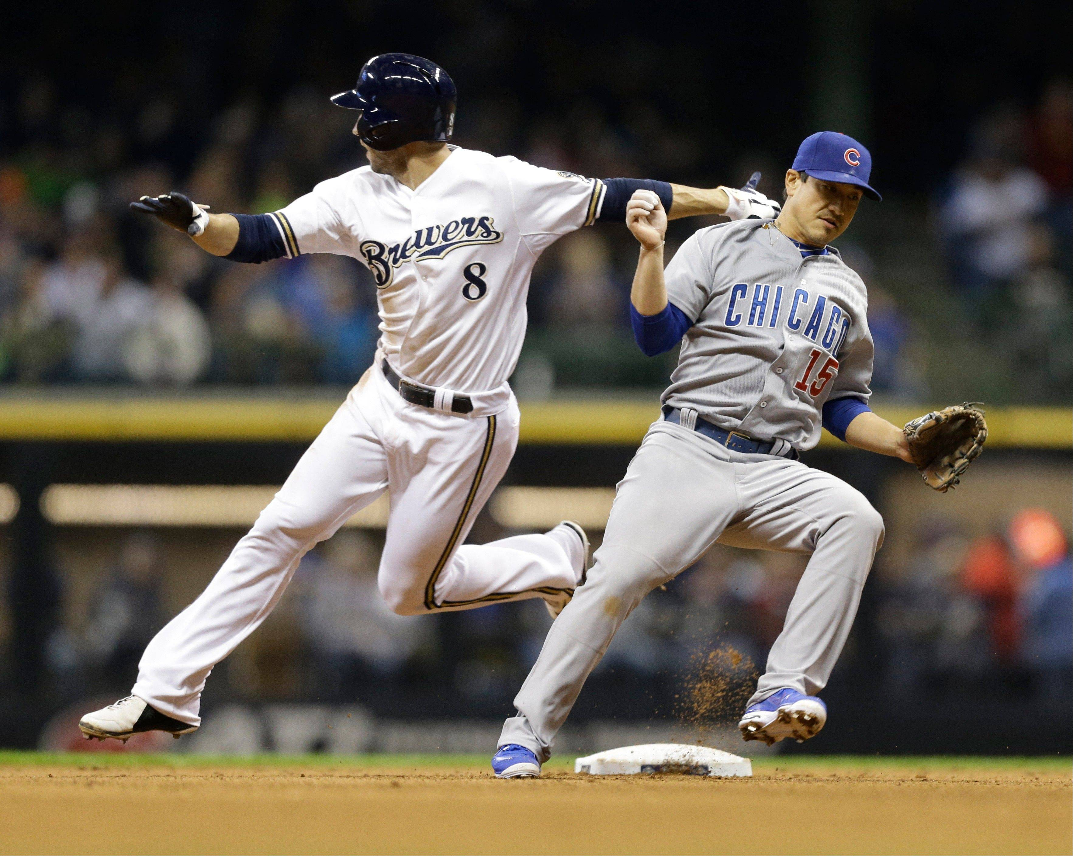 Chicago Cubs' Darwin Barney (15) moves out of the way as Milwaukee Brewers' Ryan Braun (8) rounds second base after a throwing error by Cubs starting pitcher Edwin Jackson during the 6th inning Saturday.