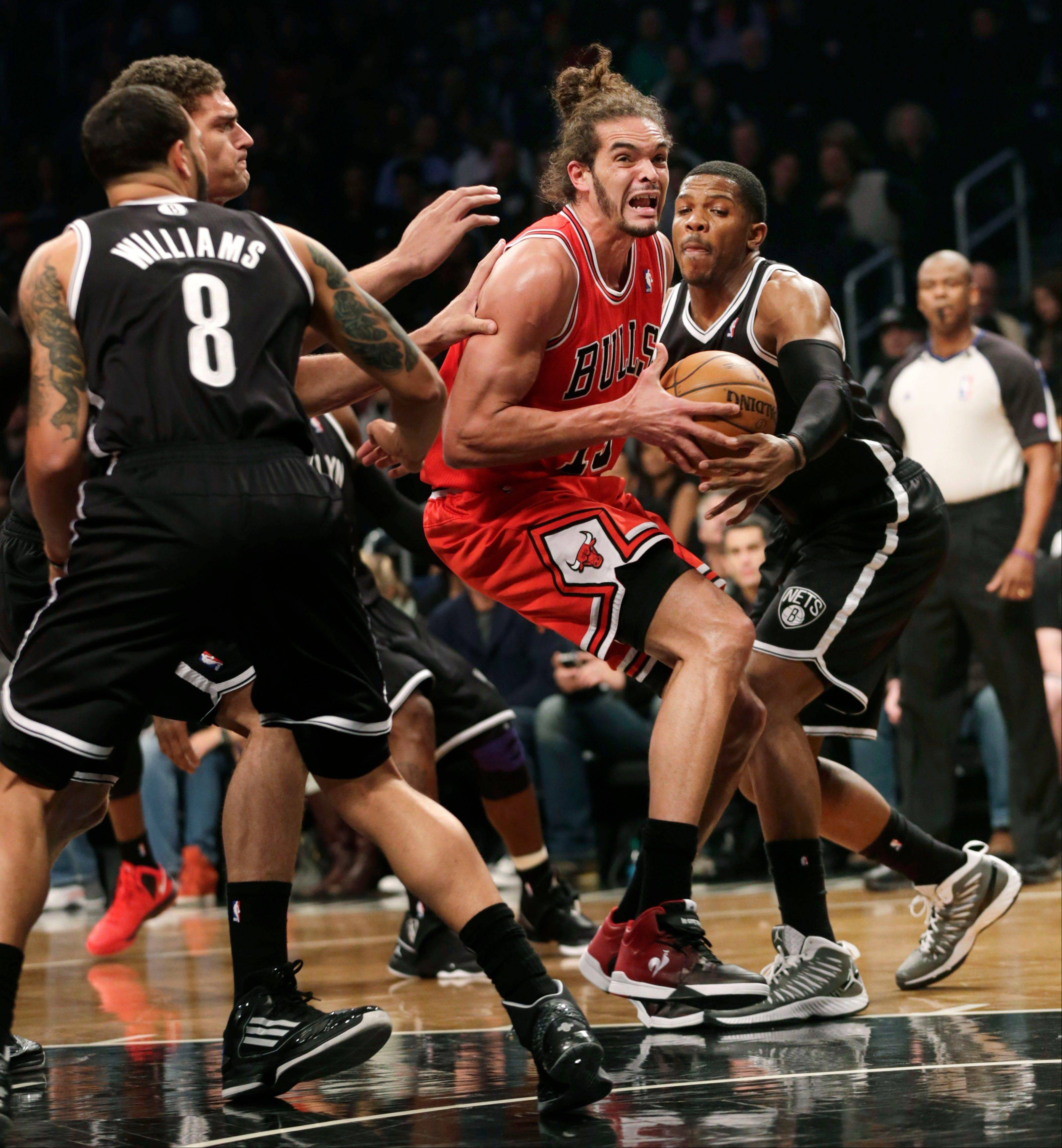 Chicago Bulls' Joakim Noah, second from right, tries to get through the Brooklyn Nets defense, including Joe Johnson, right, during the first quarter.