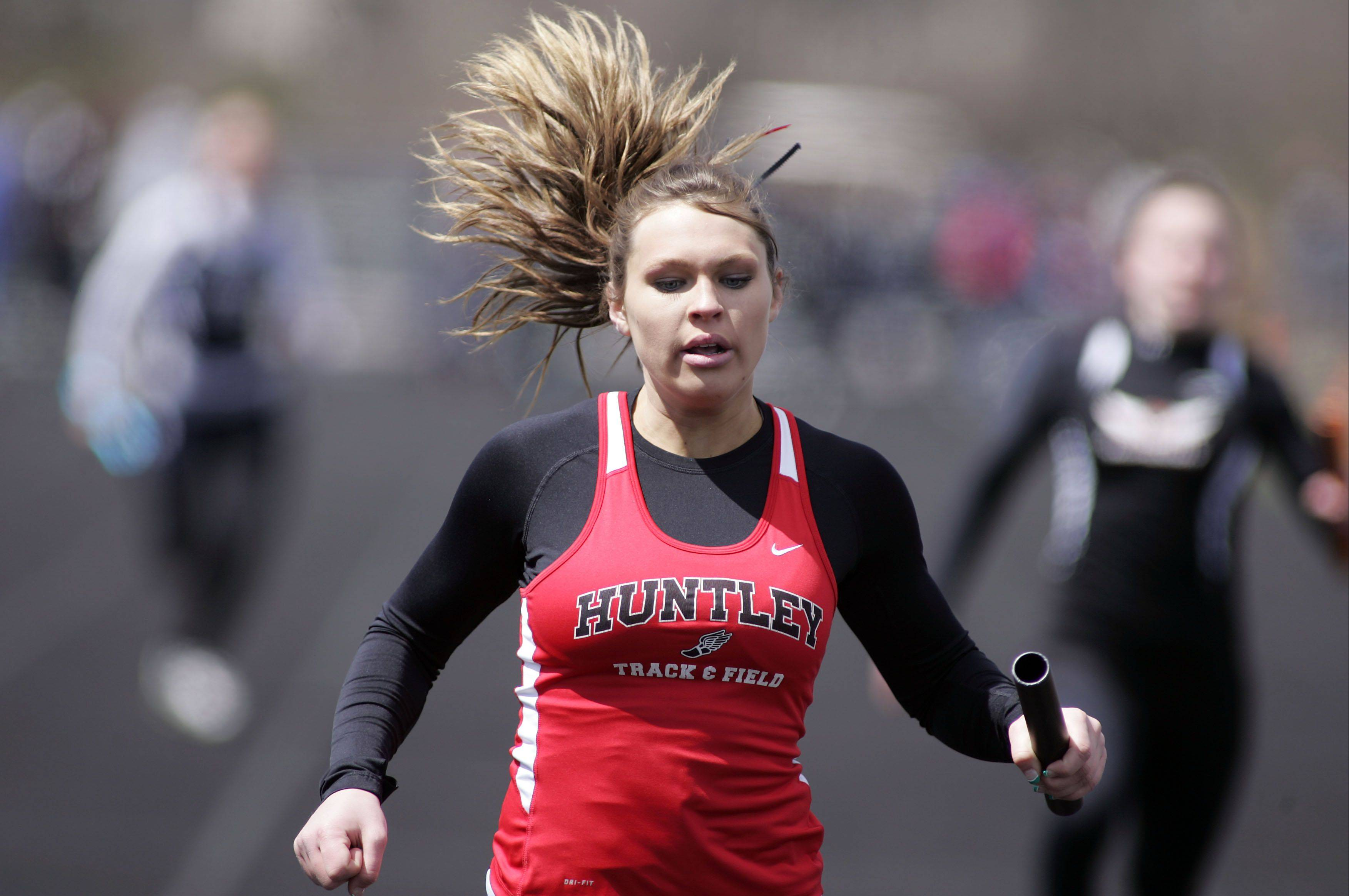 Taylor Schau of Huntley finishes first in the 400 relay during the McHenry County boys and girls track meet Saturday at Cary-Grove High School in Cary.