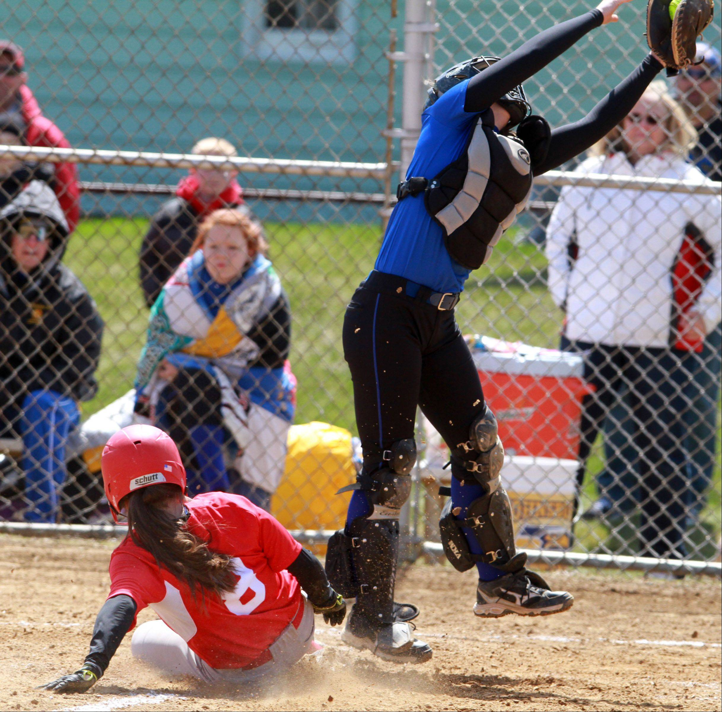 Mundelein's Maddie Zazas slides home safely as Johnsburg's catcher Rachael Barnettez reaches for the throw at Mundelein on Saturday.