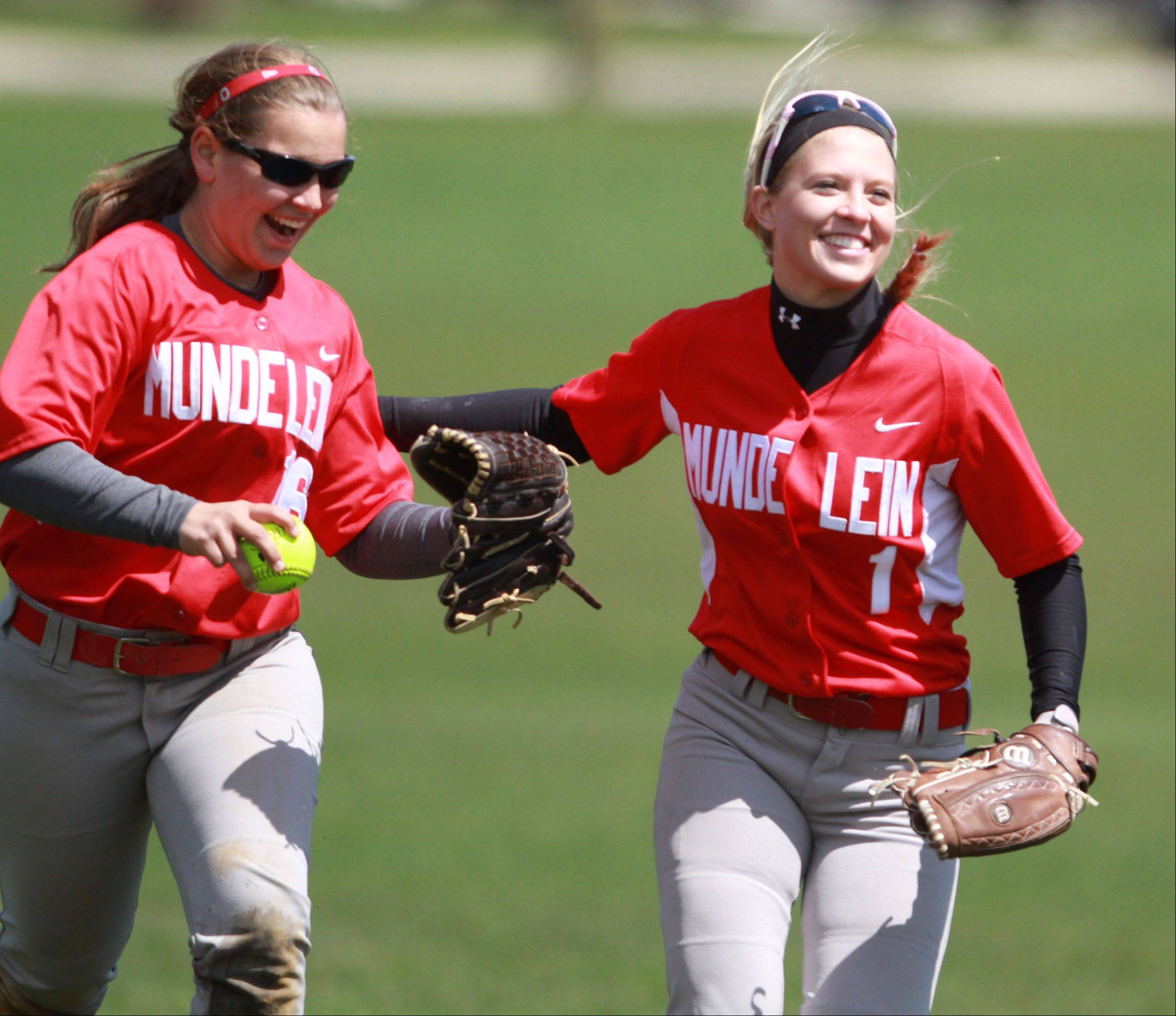 Mundelein's Hannah Bulgart, left, gets a hand from teammate Chloe Peterson after Bulgart make a difficult catch to end the inning against Johnsburg at Mundelein on Saturday.