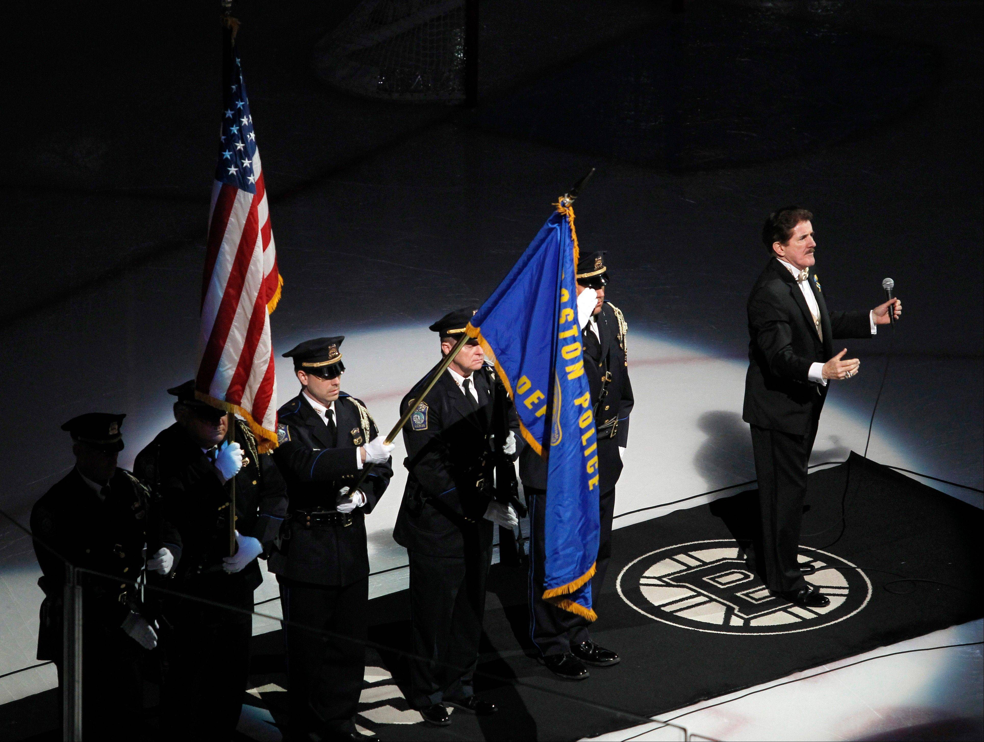 Rene Rancourt, right, conducts the crowd in the singing of the national anthem as the Boston Police honor guard presents the colors before the start of an NHL hockey game between the Pittsburgh Penguins and Boston Bruins, Saturday, April 20, 2013, in Boston.