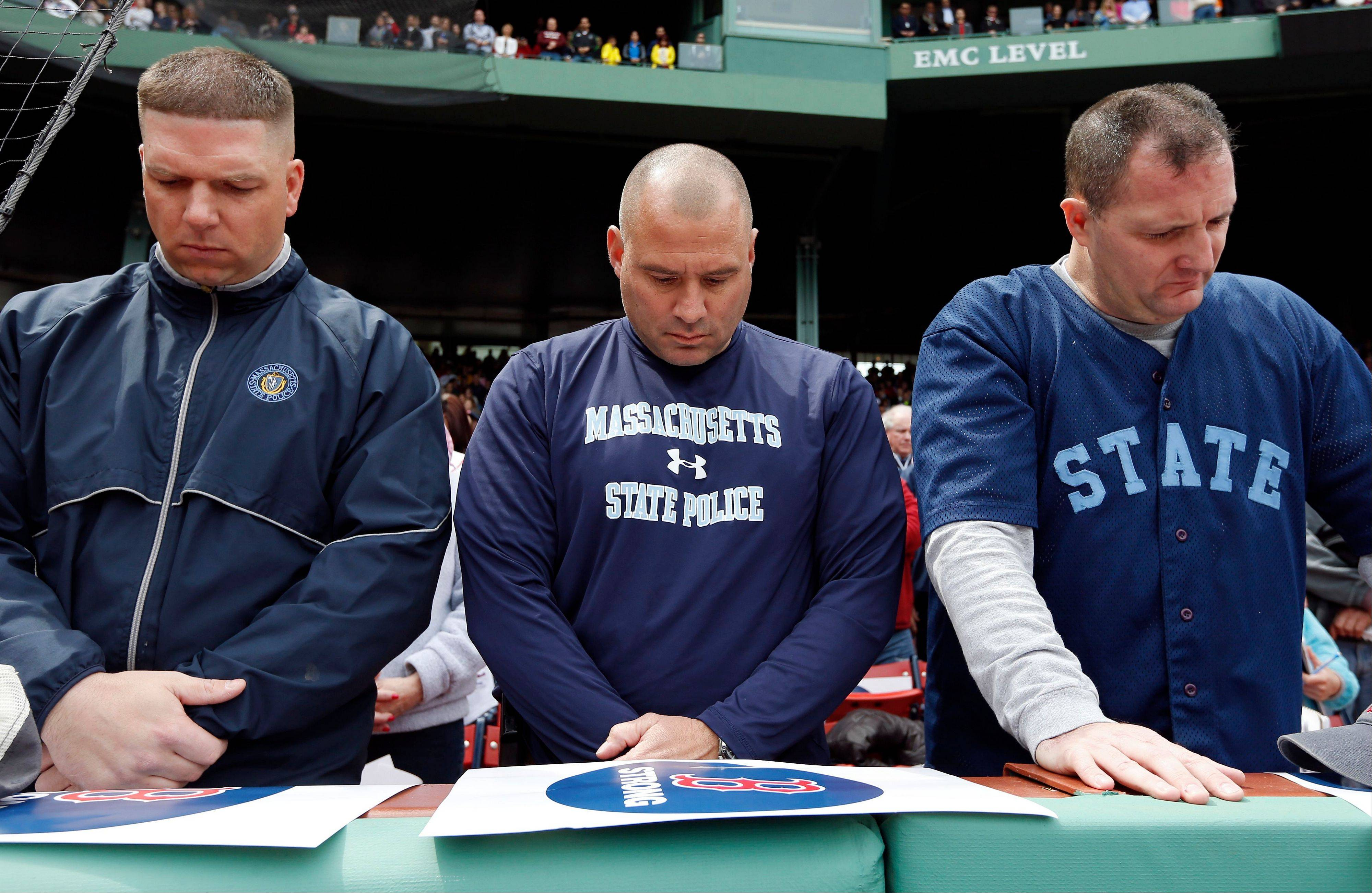 Three members of the Massachusetts State Police bow their head during a moment of silence before a baseball game between the Boston Red Sox and the Kansas City Royals in Boston, Saturday, April 20, 2013.