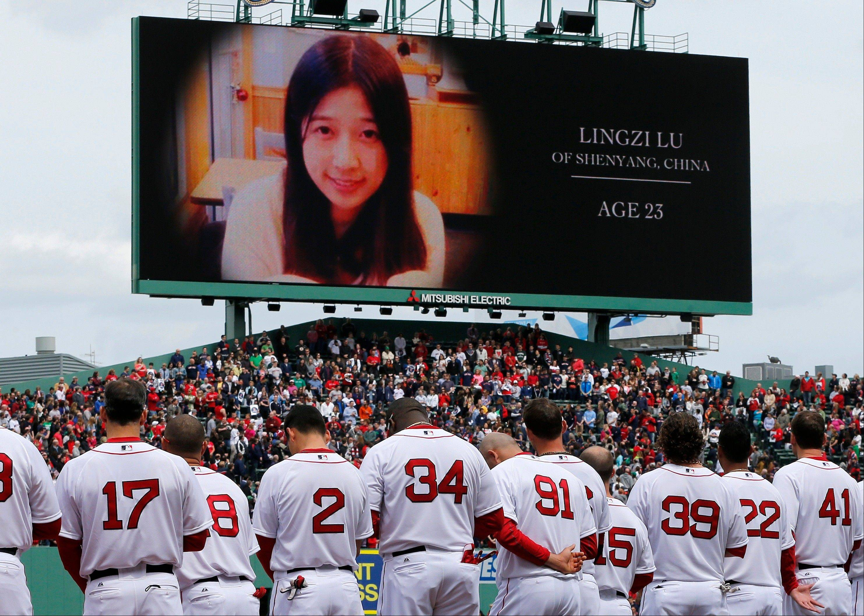 The Boston Red Sox stand during tribute to Boston Marathon bombing victims, including Chinese student Lingzi Lu, before a baseball game against the Kansas City Royals in Boston, Saturday, April 20, 2013.
