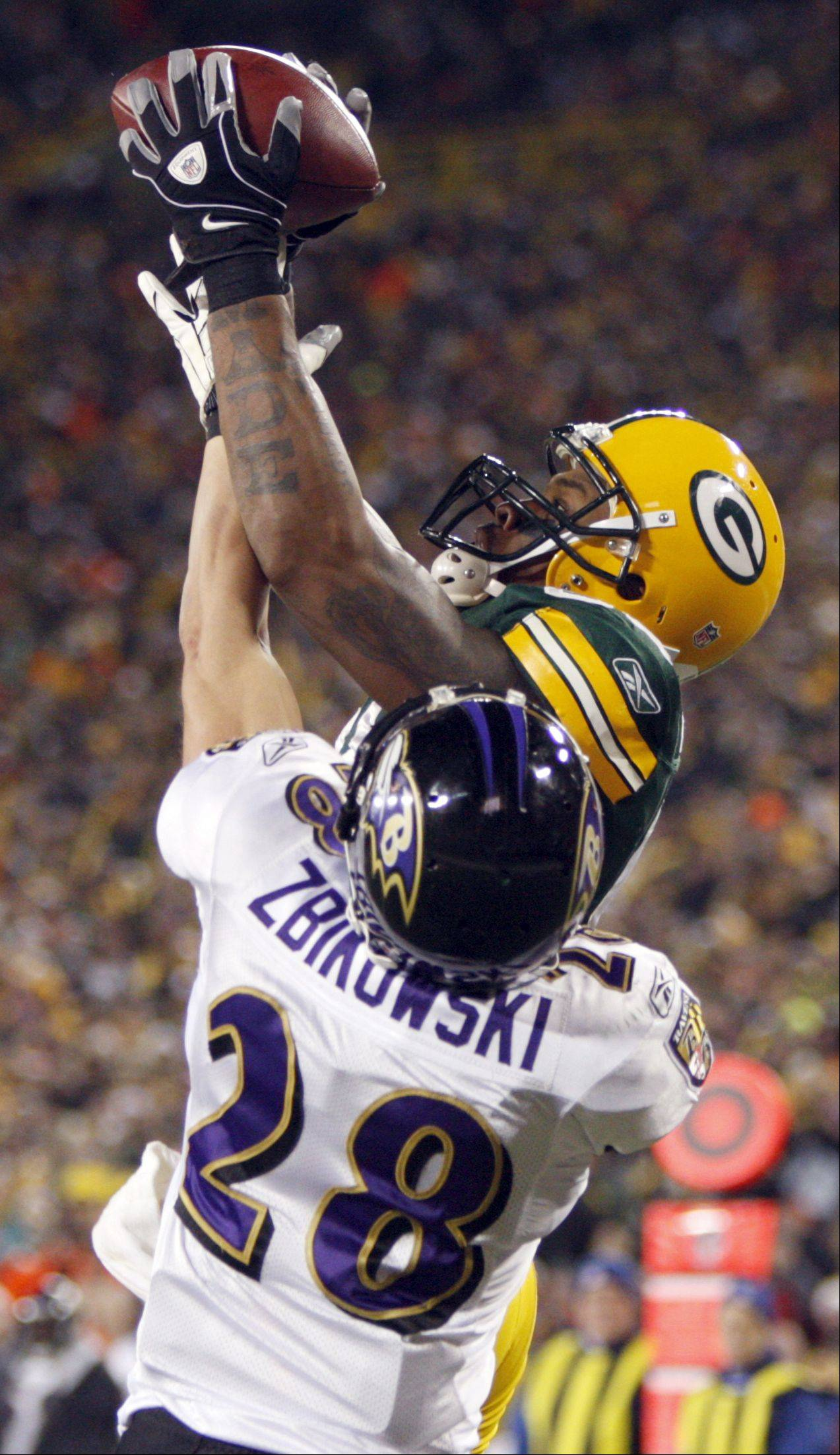 Green Bay Packers' Jermichael Finley pulls in a touchdown pass as former Baltimore Ravens safety Tom Zbikowski tries to break it up.