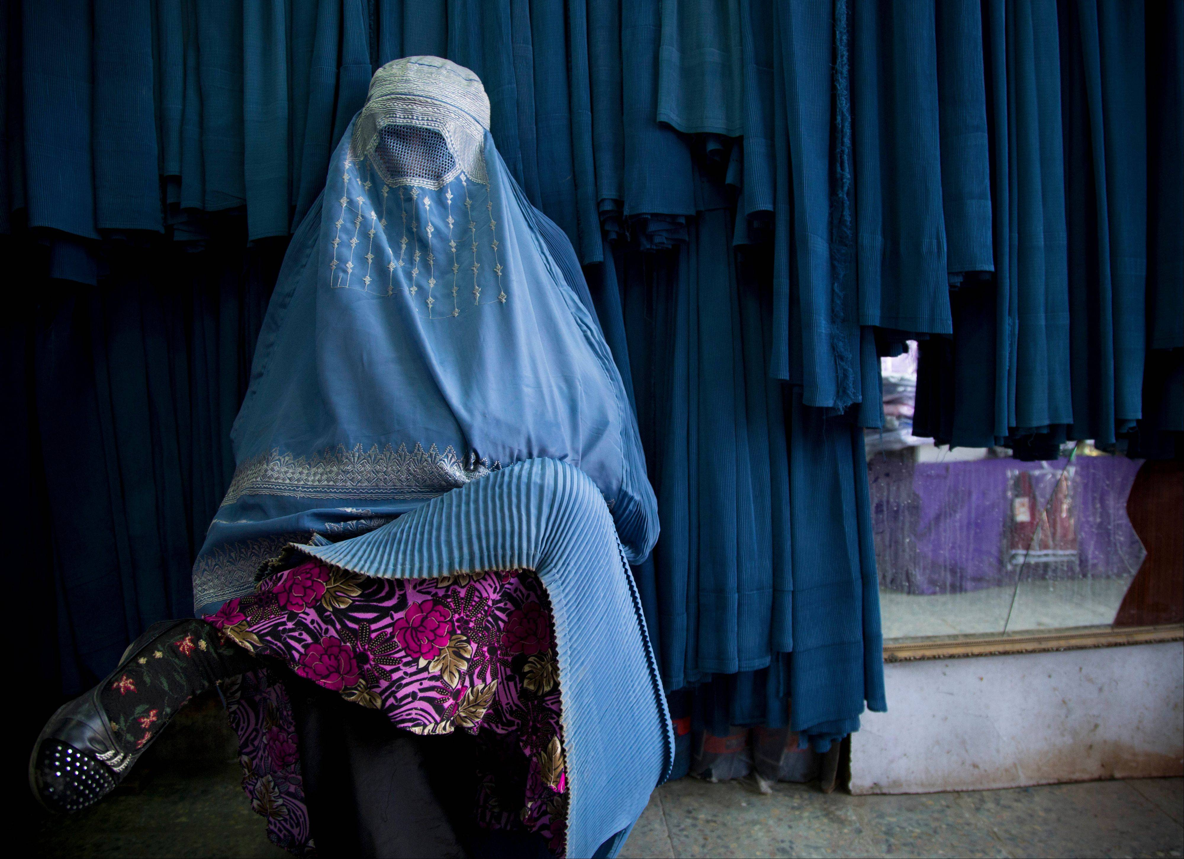 An Afghan woman waits to get in line to try on a new burqa at a shop in the old town of Kabul, Afghanistan. Despite advances in women's rights, Afghanistan remains a deeply conservative country and most women continue to wear the Burqa. But tradesmen say times are changing in Kabul at least, with demand for burqas declining as young women going to school and taking office jobs refuse to wear the cumbersome garments.