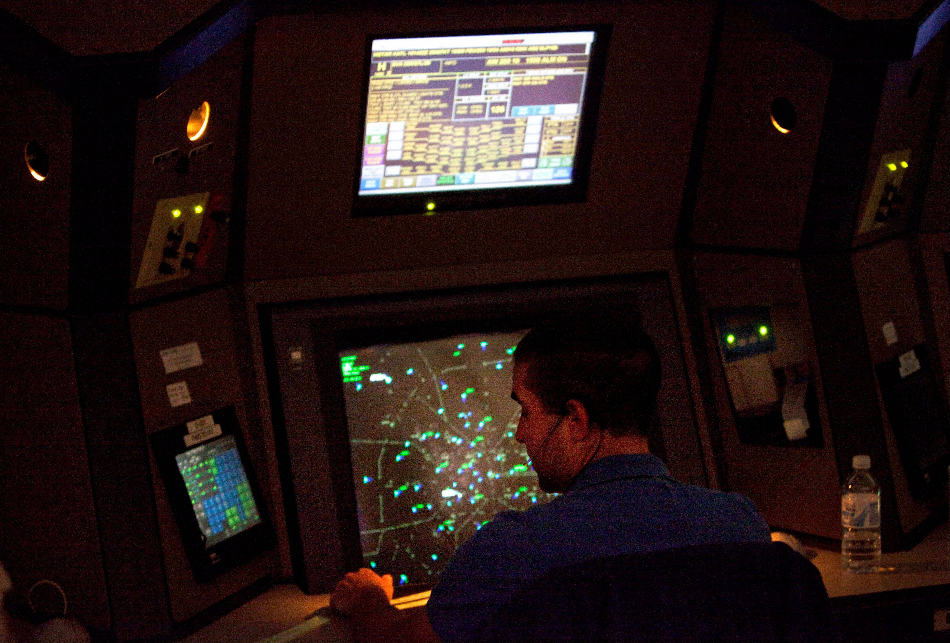 This April 18, 2011 file photo shows an air traffic controller working in a terminal radar approach control room at the Atlanta TRACON in Peachtree City, Ga. As Air traffic controller furloughs kicked in on Sunday, it was largely uneventful with most flights on time. However, Monday could be a different story when air travel ramps up.