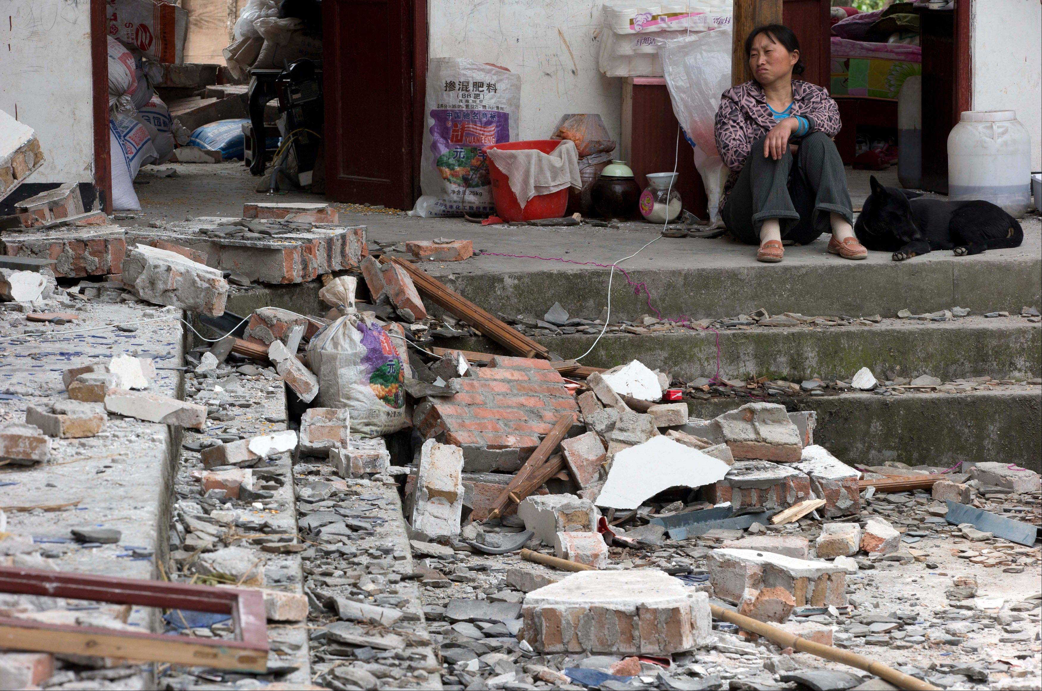 A woman looks over at her destroyed house in Gucheng village in Longmen county of southwestern China�s Sichuan province, Sunday, April 21, 2013. Rescuers and relief teams struggled to rush supplies into the rural hills of China�s Sichuan province Sunday after an earthquake prompted frightened survivors to spend a night in cars, tents and makeshift shelters.